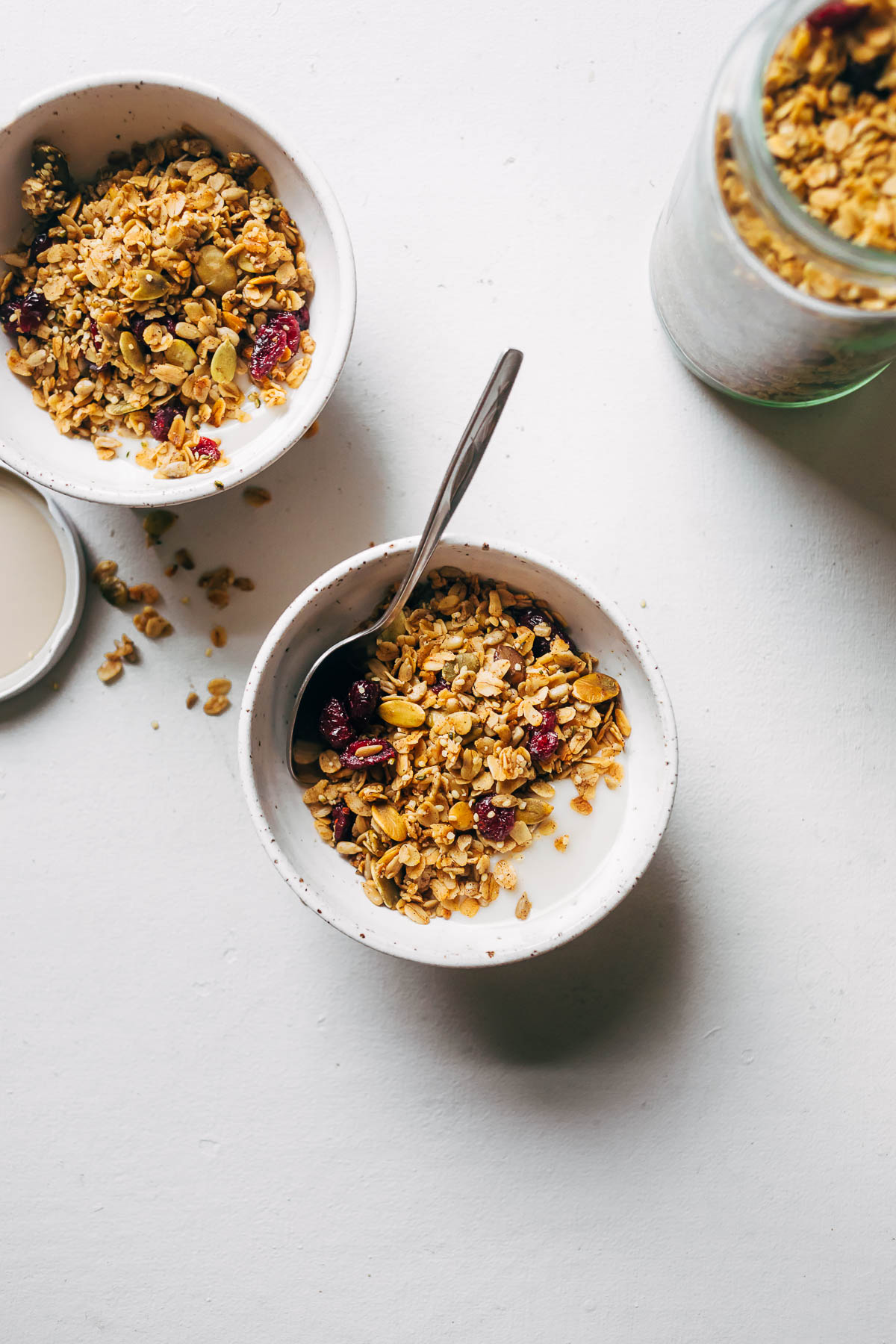 Two servings of granola in bowls on a white surface.