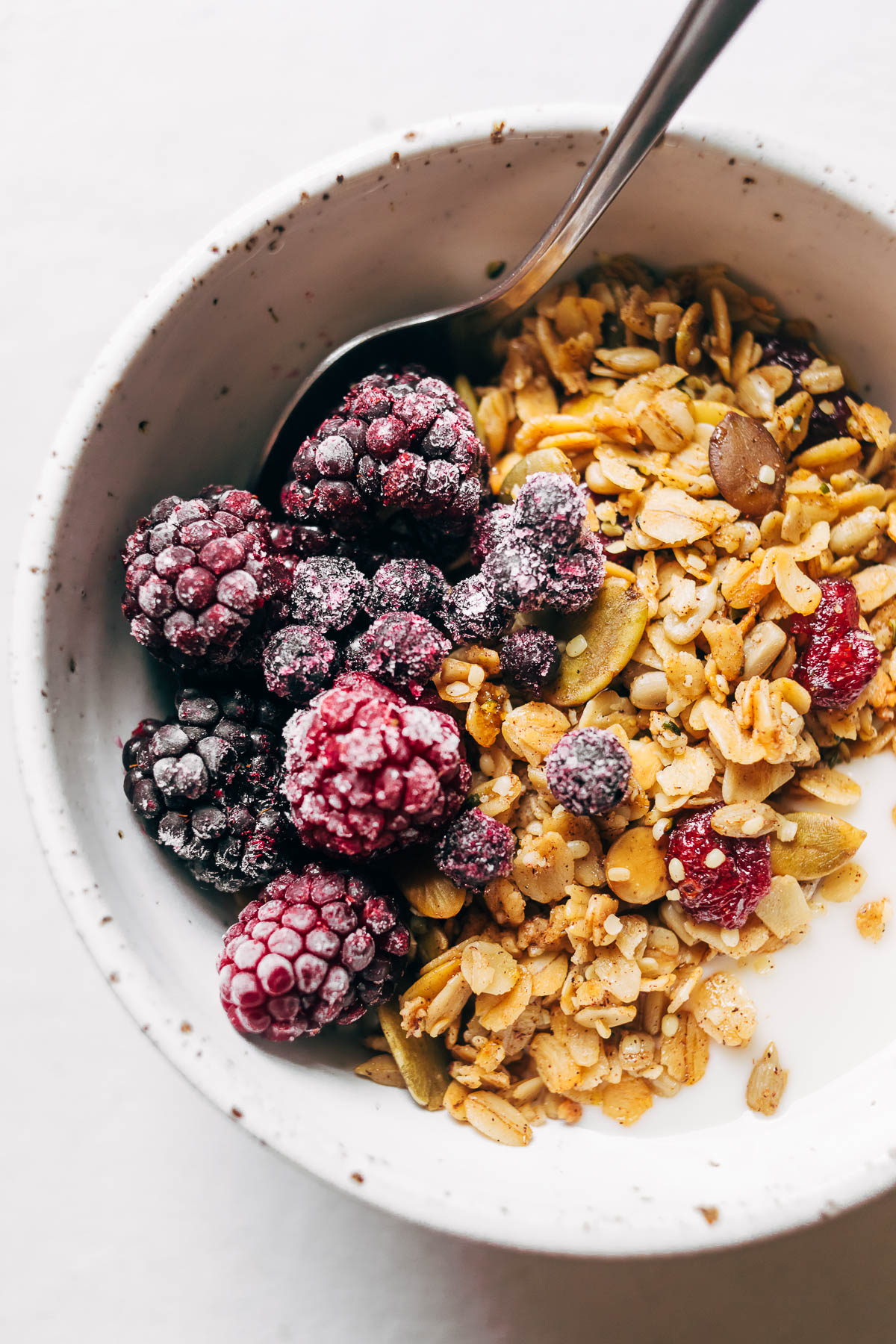 Close up of a bowl of hemp granola with milk and frozen berries.