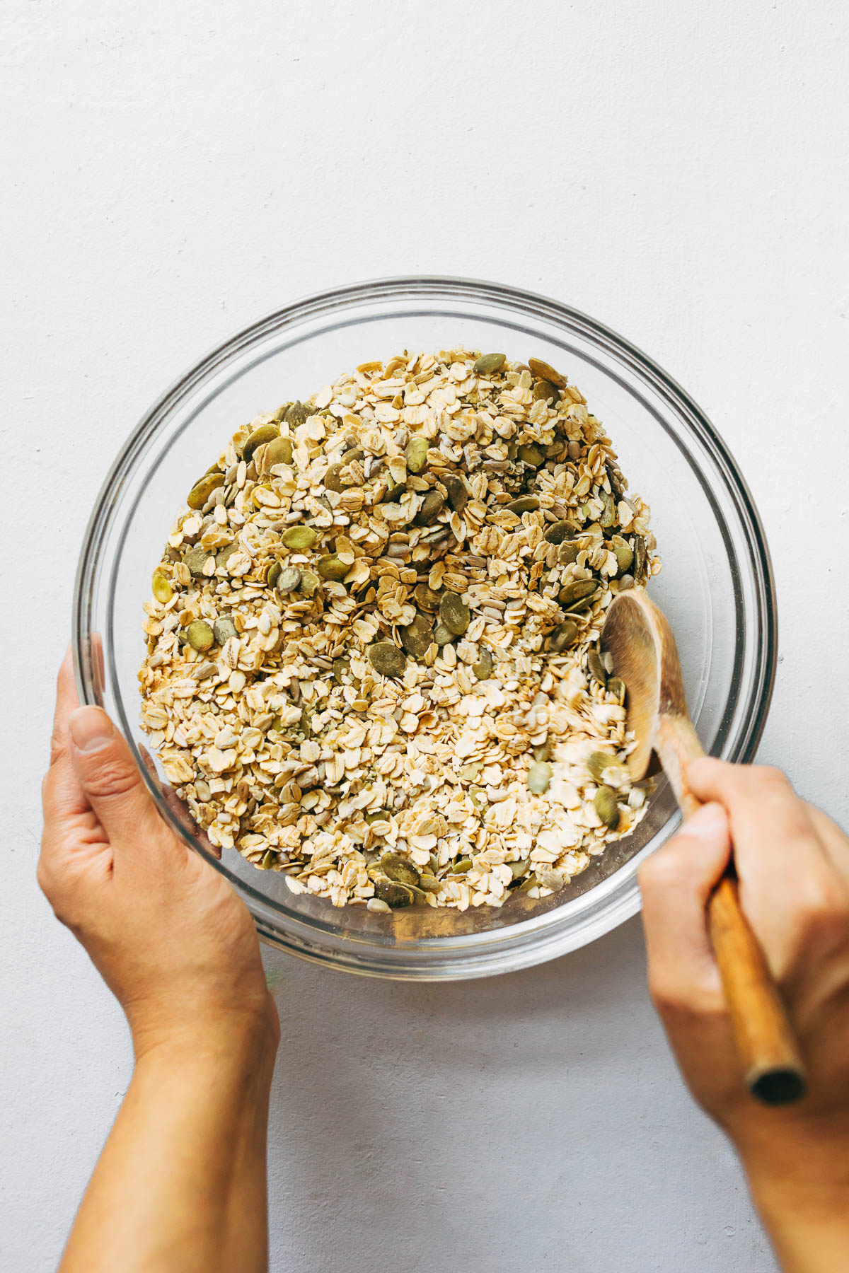 A hand mixing oats and seeds with a wooden spoon in a large glass bowl.