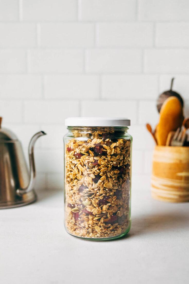 A jar of hemp granola on a white countertop.