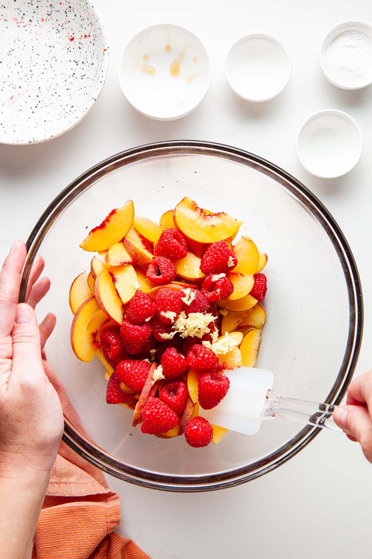 Raspberries and flavourings being mixed into the bowl of peaches.