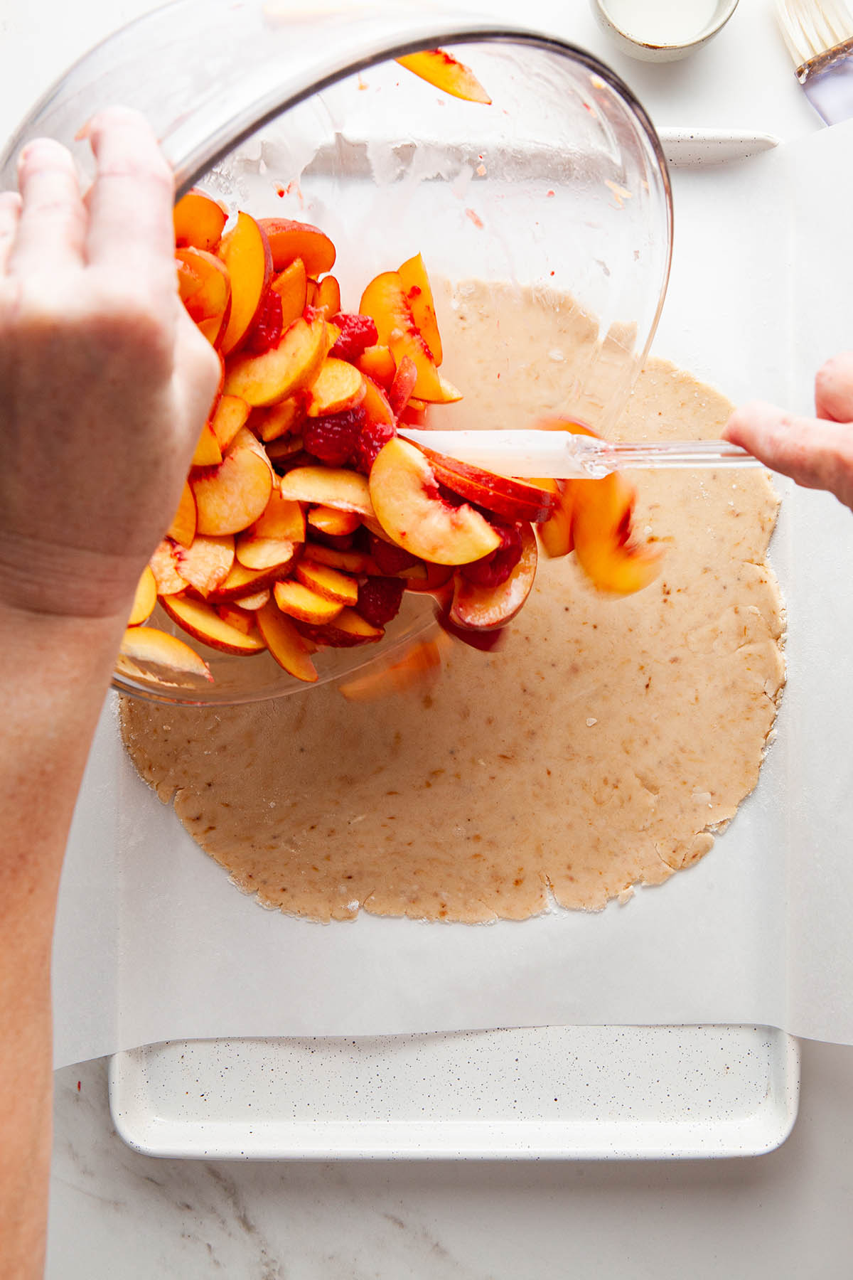Peach filling being added to the middle of the galette.