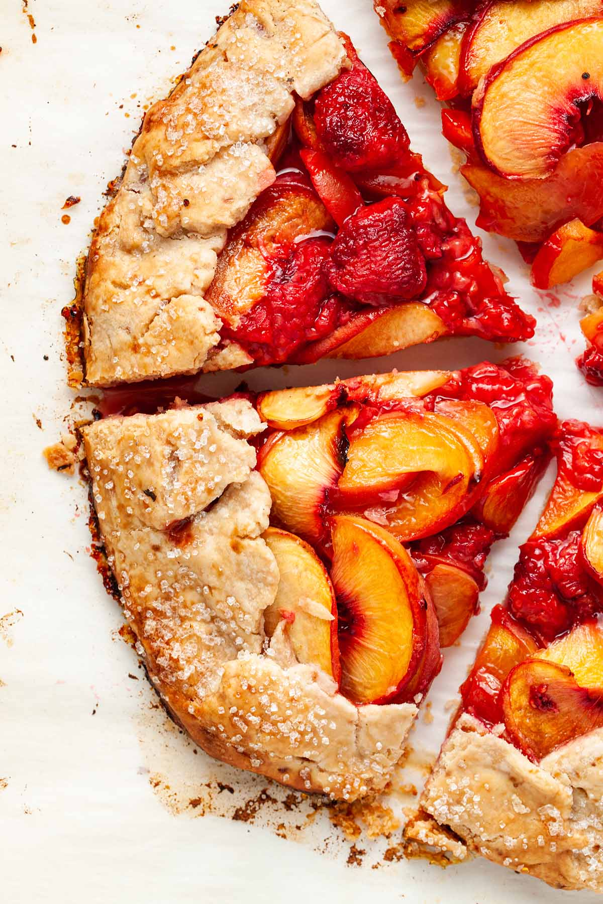 A close up of vegan peach galette, cut into triangles.