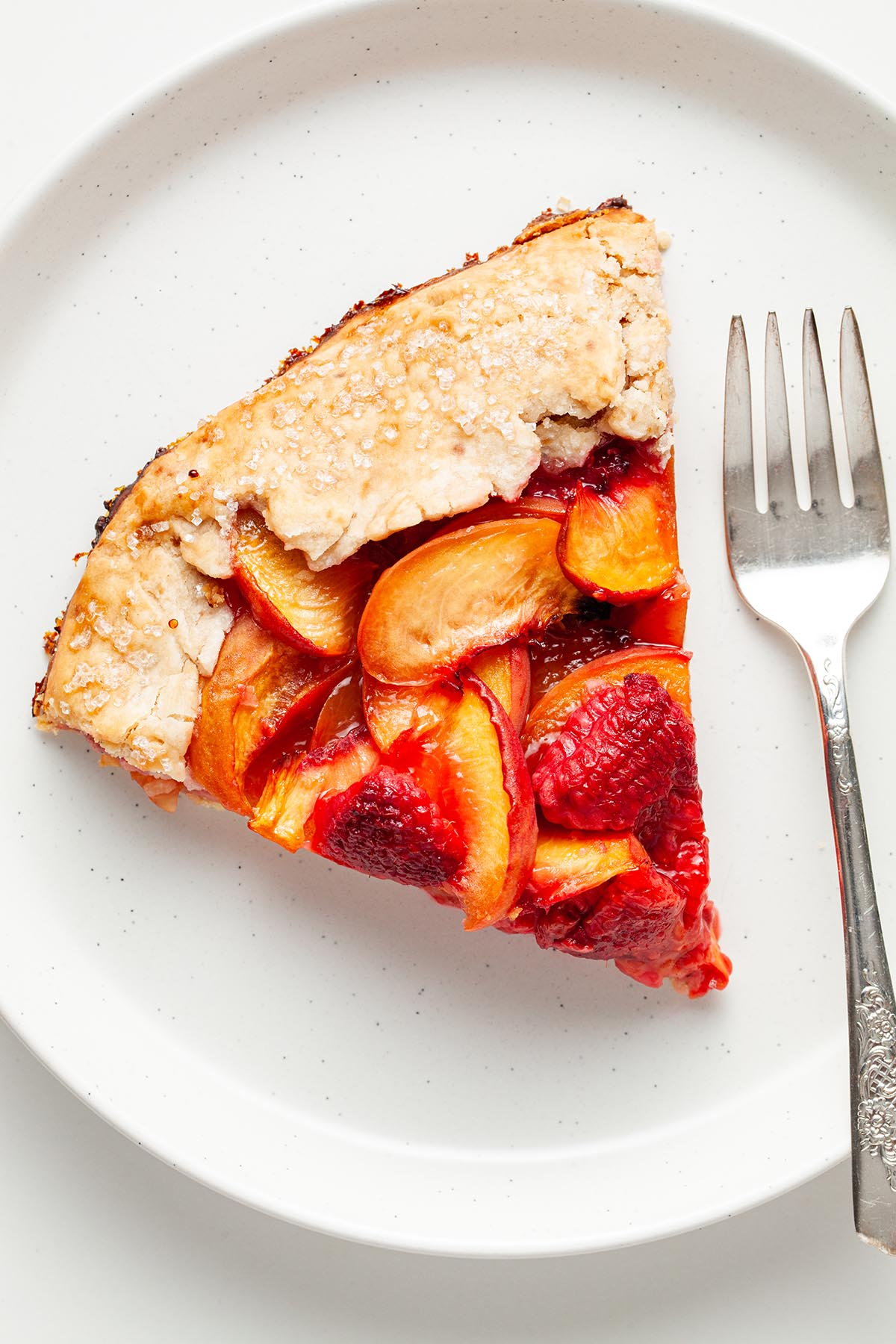 A slice of vegan peach galette on a plate with a fork.