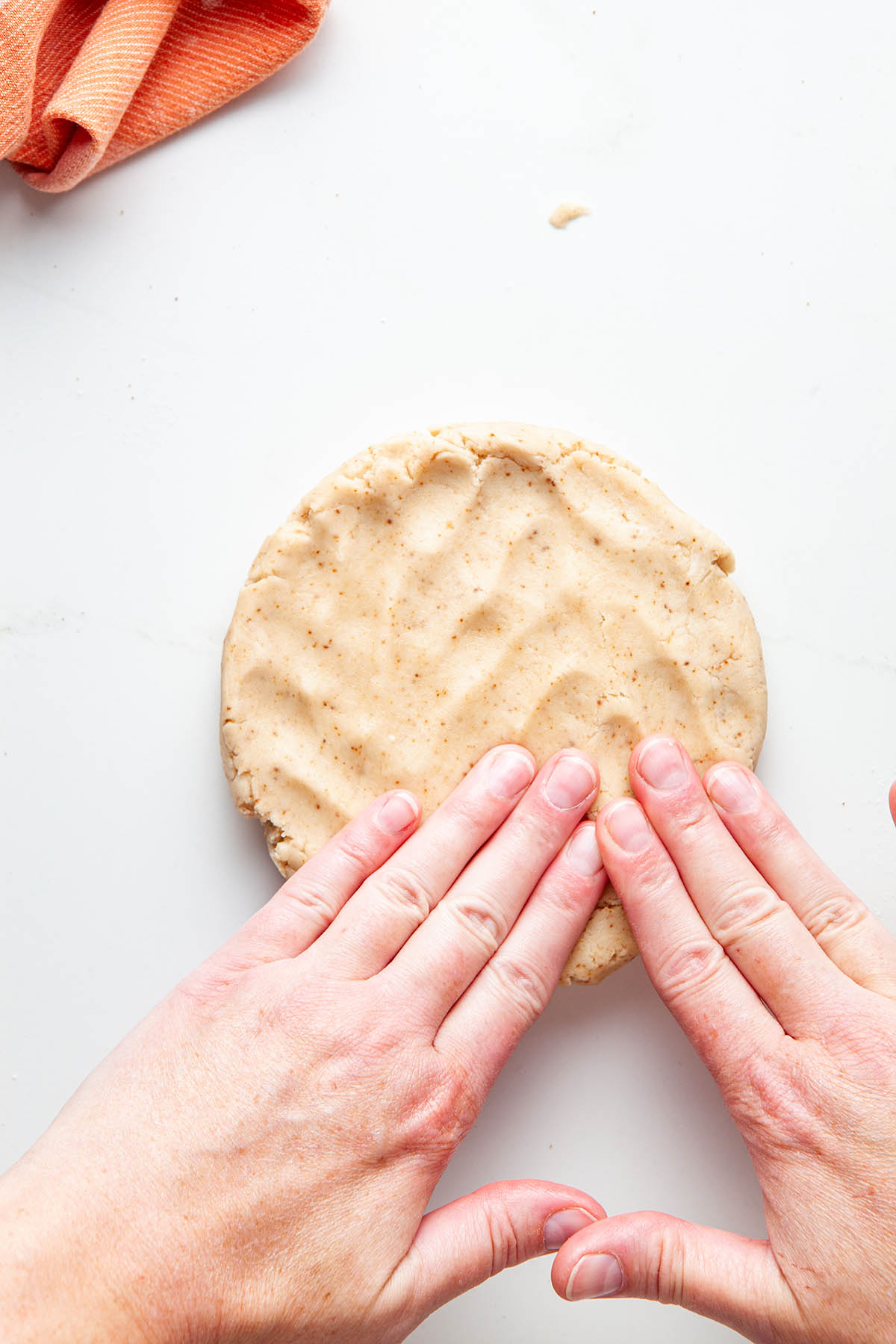 Woman's hands patting pie dough into a disc.