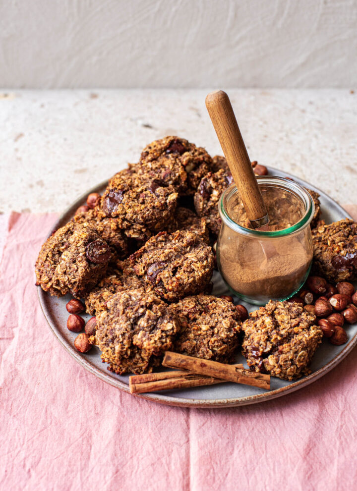 A plate full of cookies with spices in a jar.
