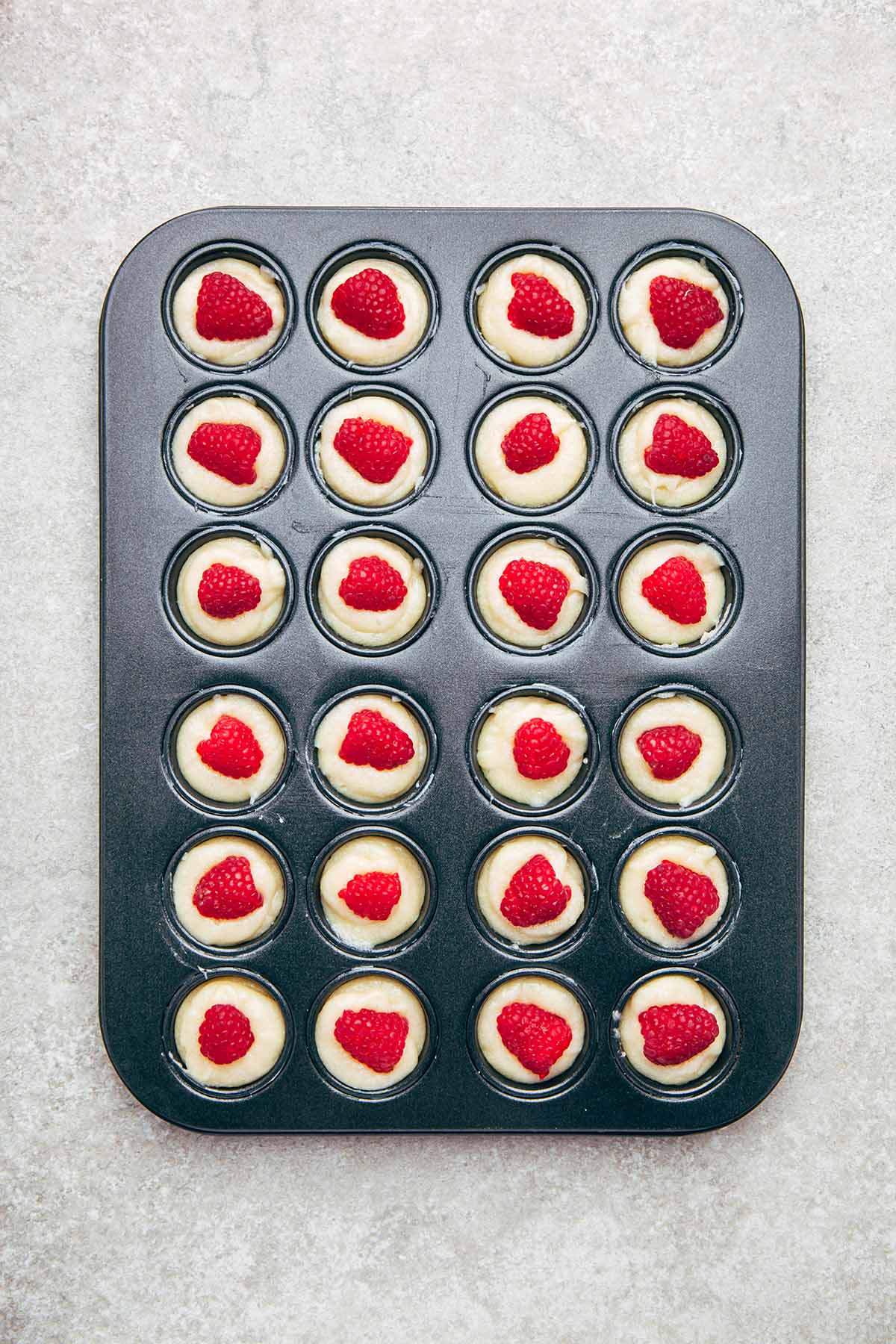 Financier batter in a mini muffin tin with raspberries pressed into the cakes.