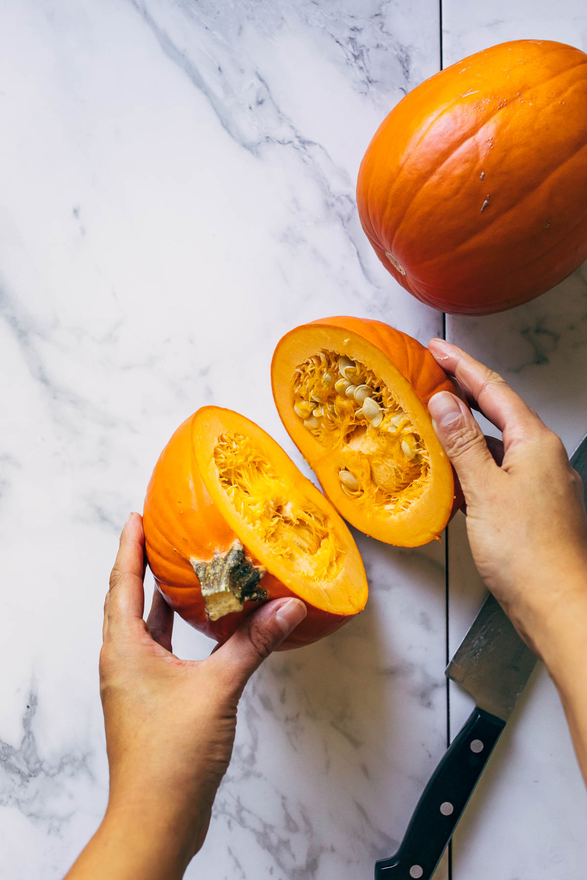 Hands opening a halved pumpkin on a marble board with a chef's knife on the board.