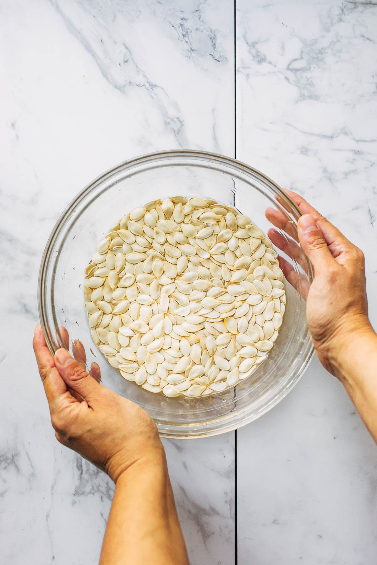 Hands holding a glass bowl of water filled with raw seeds.