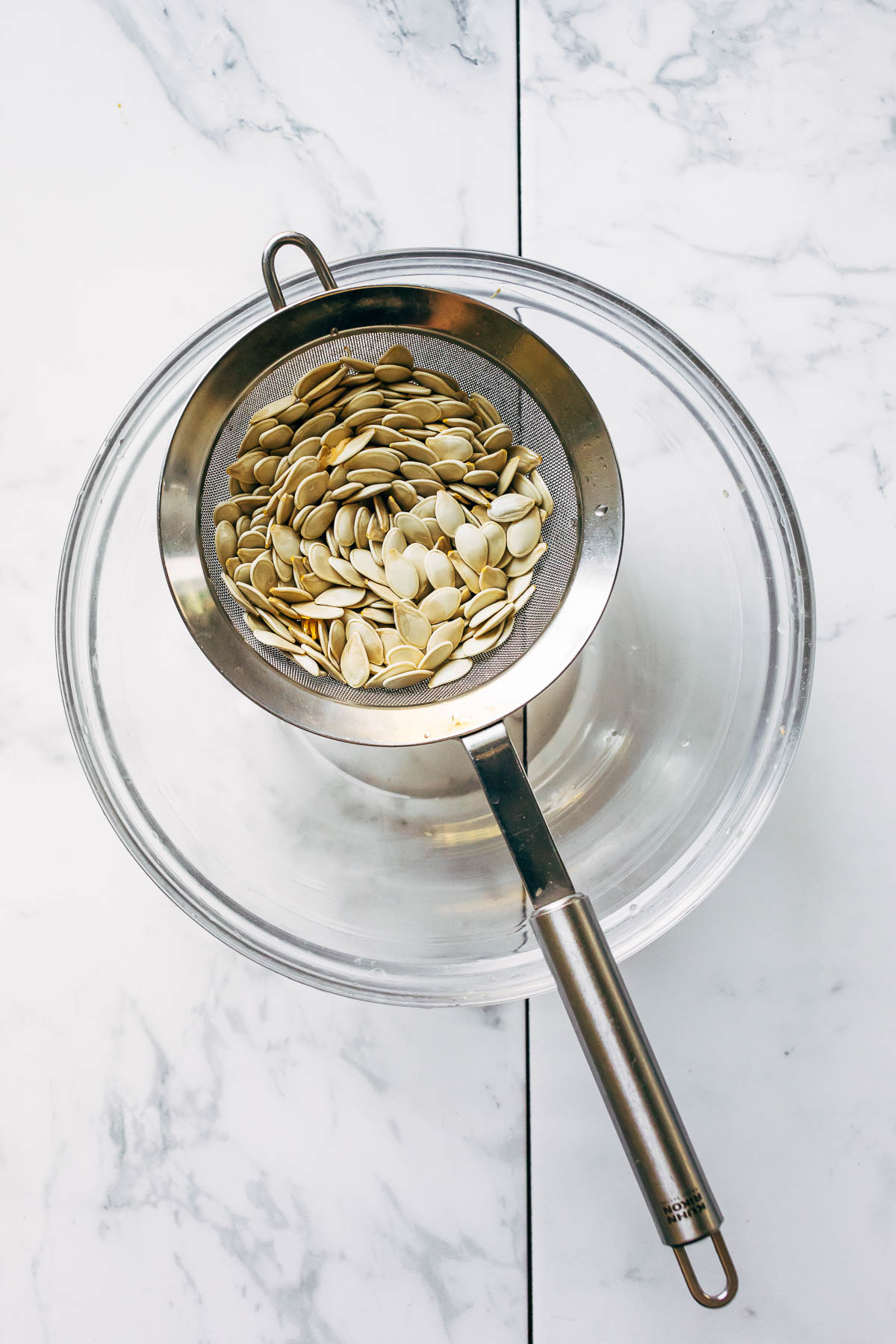 A colander filled with raw, rinsed seeds sitting over a glass bowl to drain.