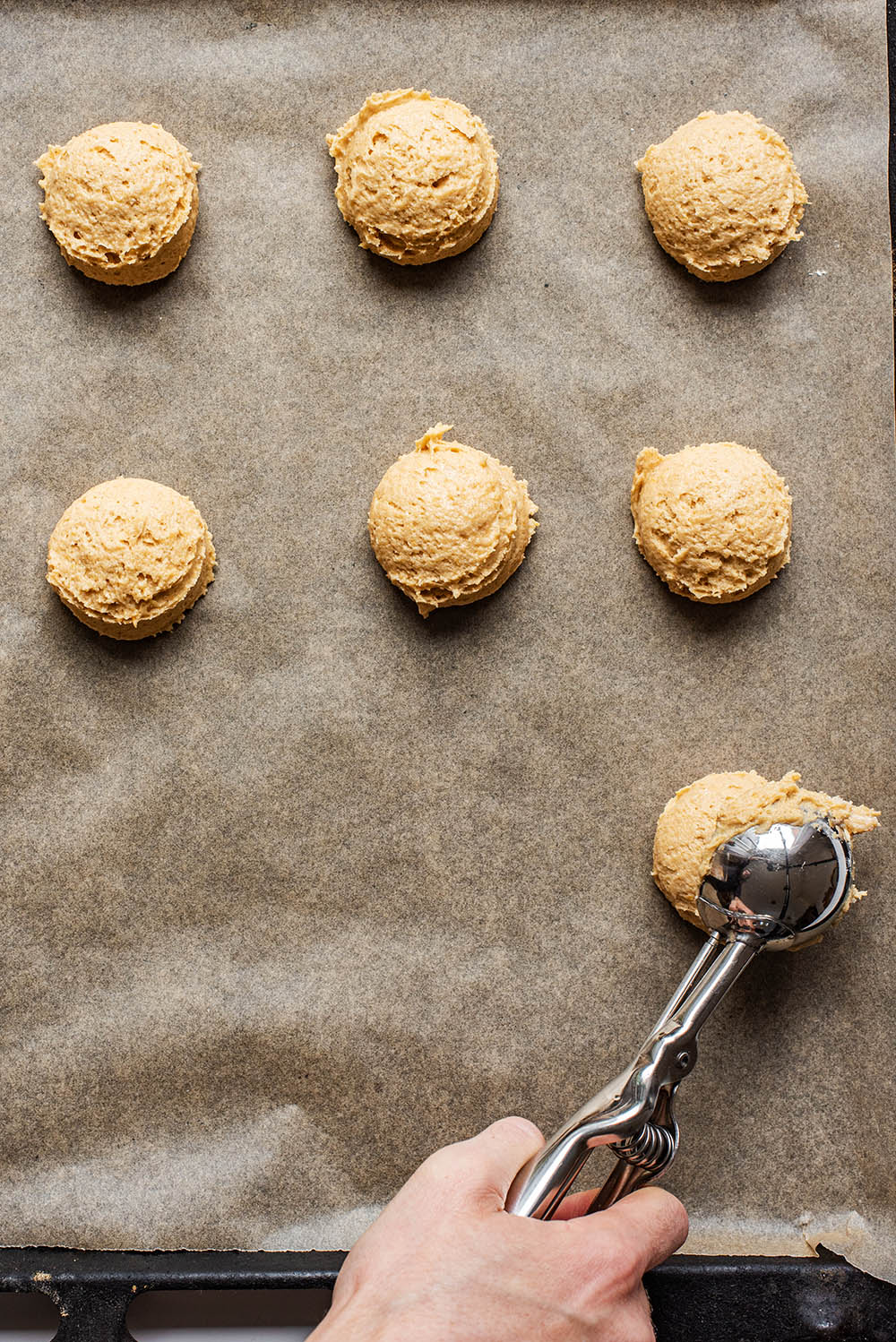 Cookies being scooped onto a lined baking sheet.