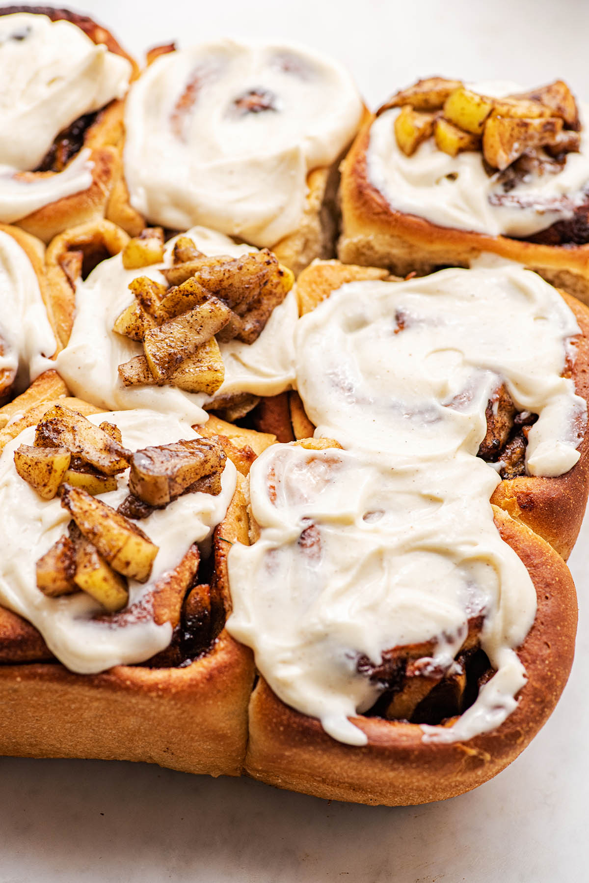 Iced cinnamon rolls topped with cooked apples.