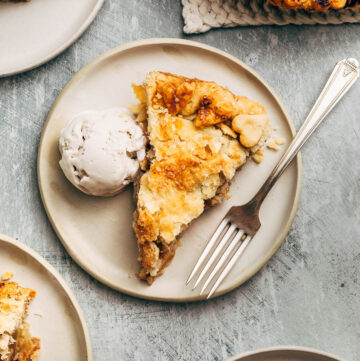 A slice of pie on a plate with ice cream.