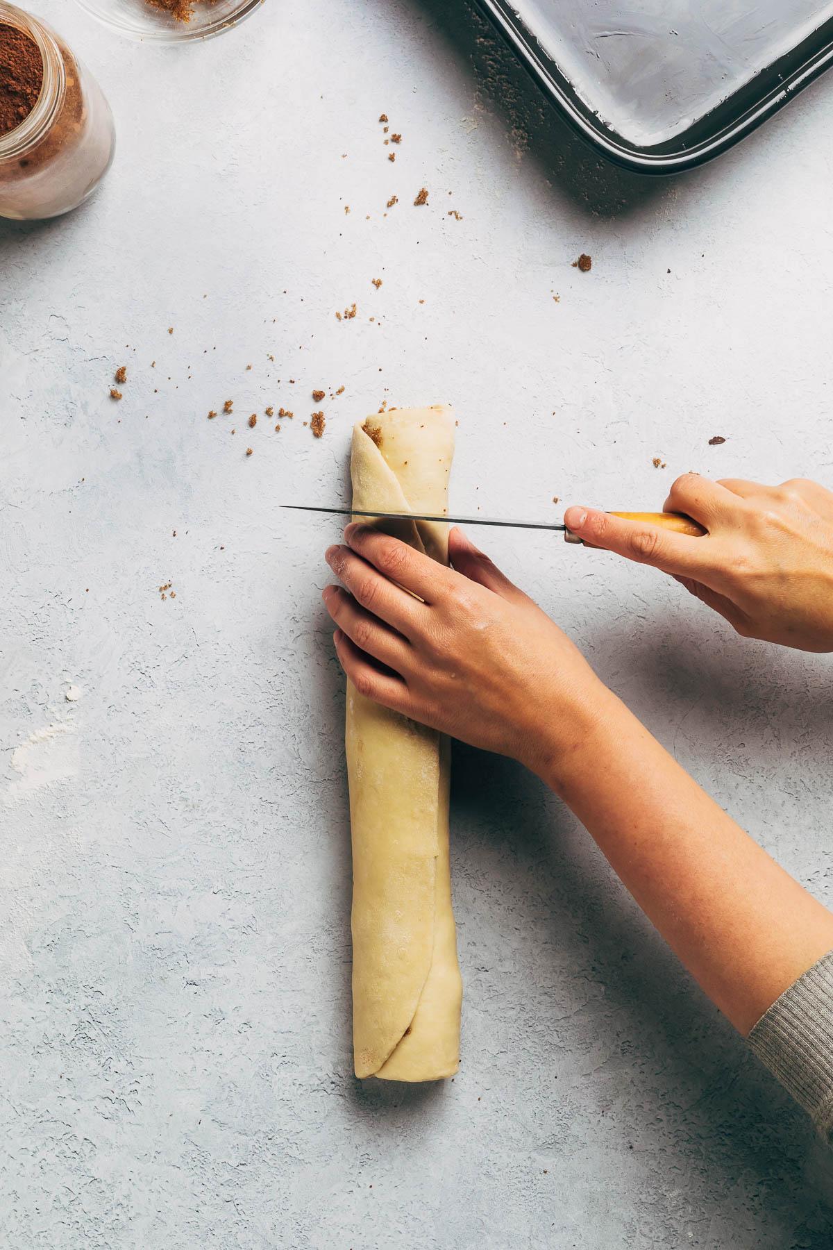 Cutting dough into individual rolls.