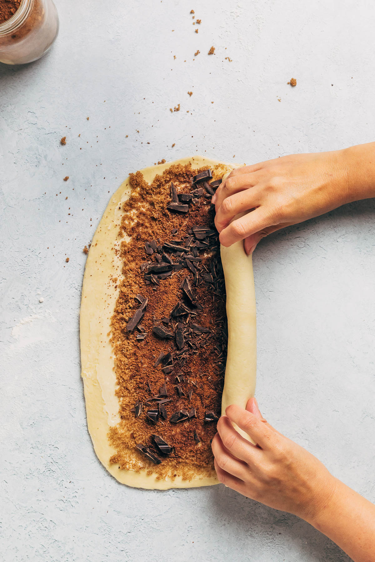 Woman's hands rolling dough into a log.