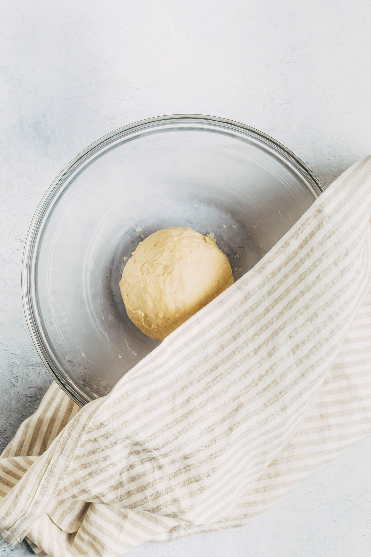 Kneaded dough in a mixing bowl, half covered by a towel.