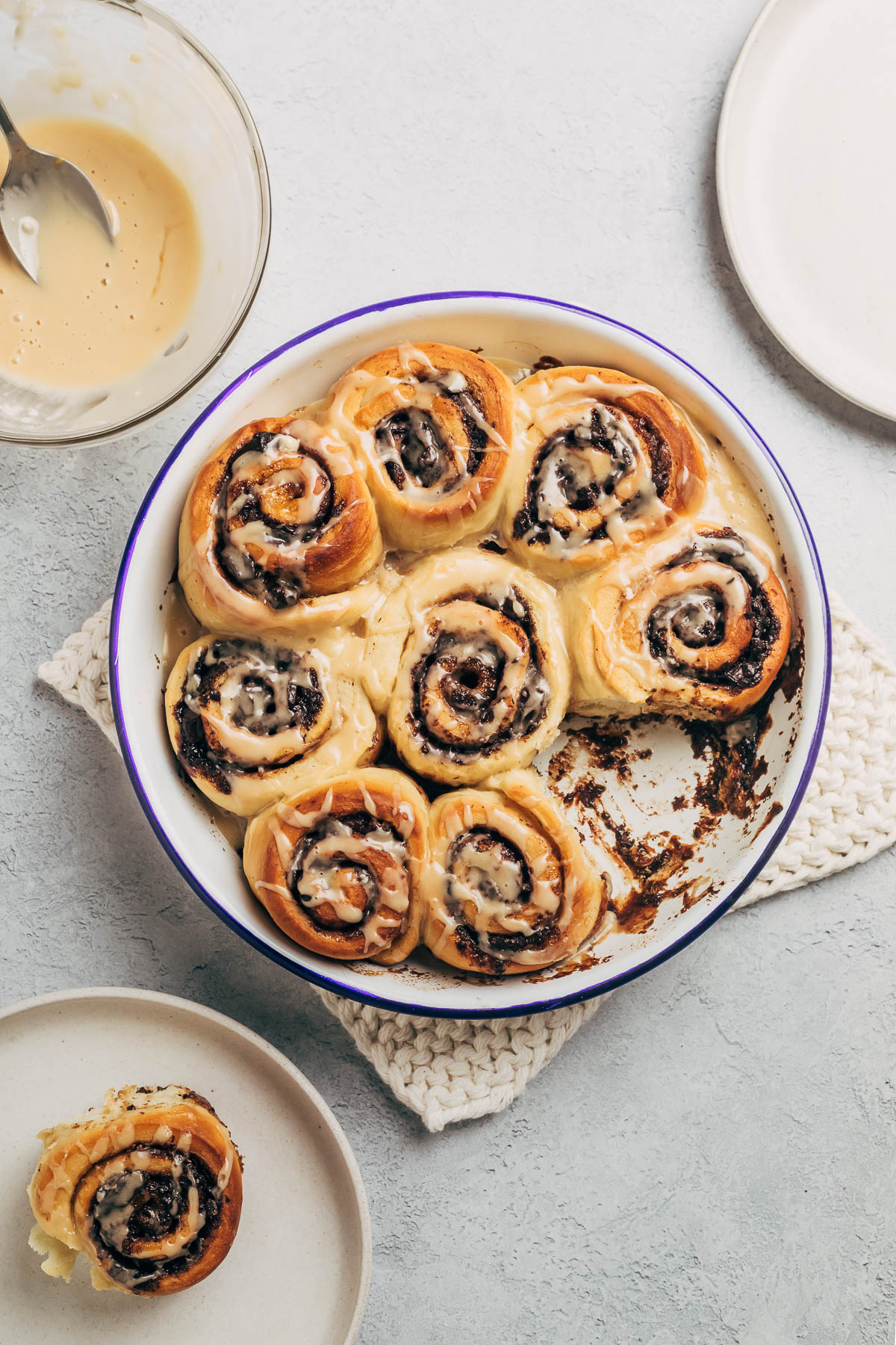 A baking tin full of baked cinnamon rolls topped with glaze.