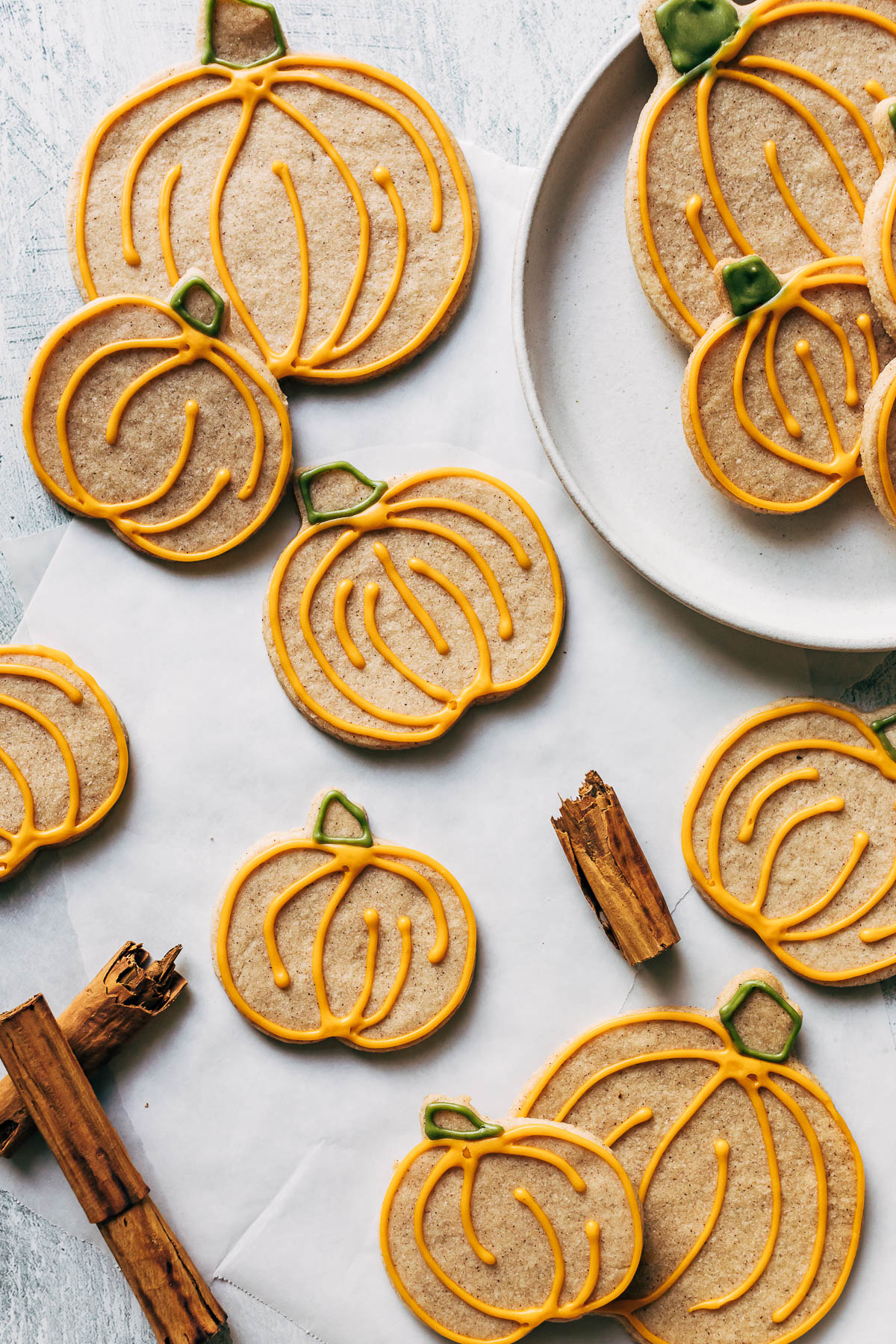 Pumpkin shaped cinnamon sugar cookies, iced, with cinnamon sticks.