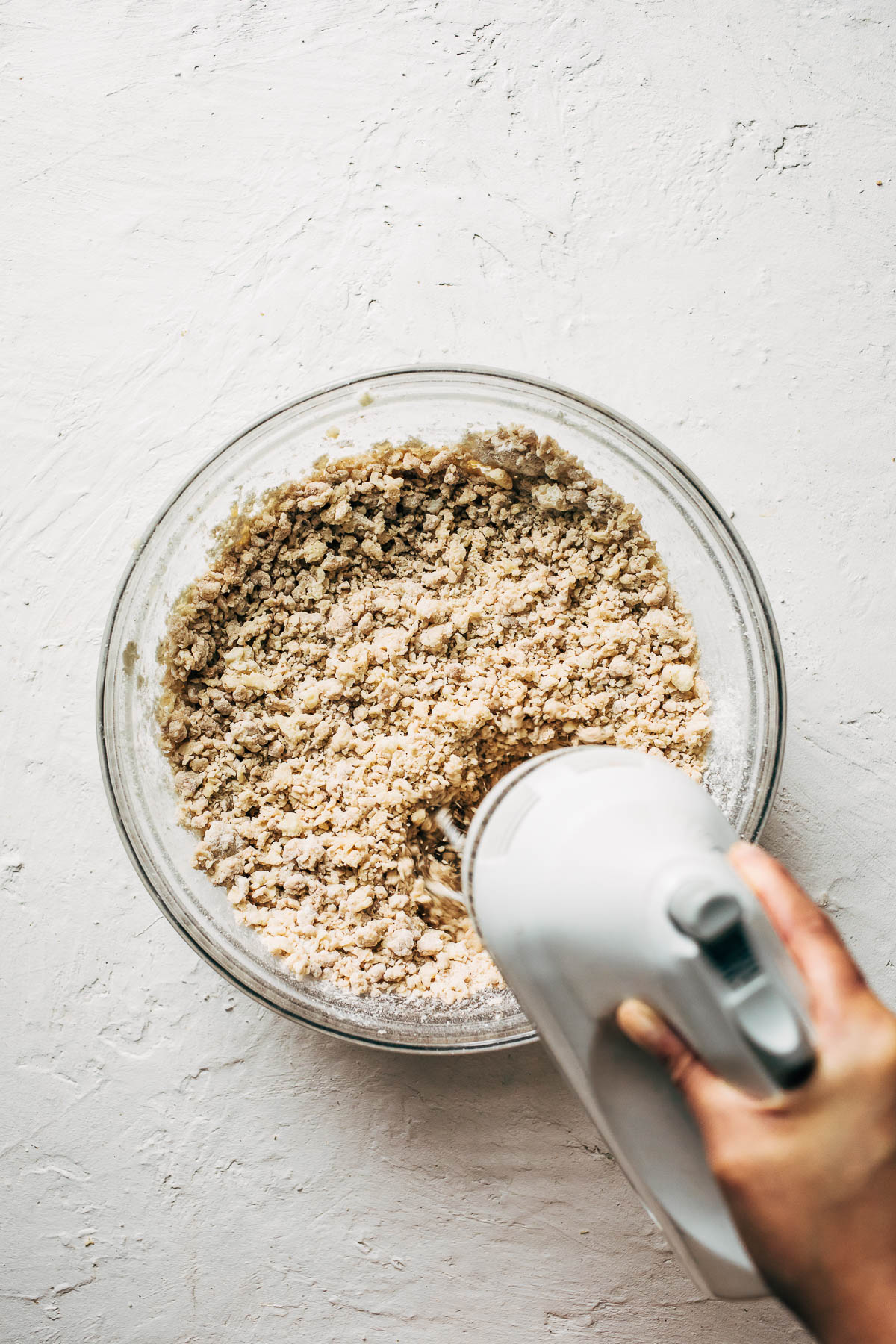 Cookie dough being mixed with an electric mixer.