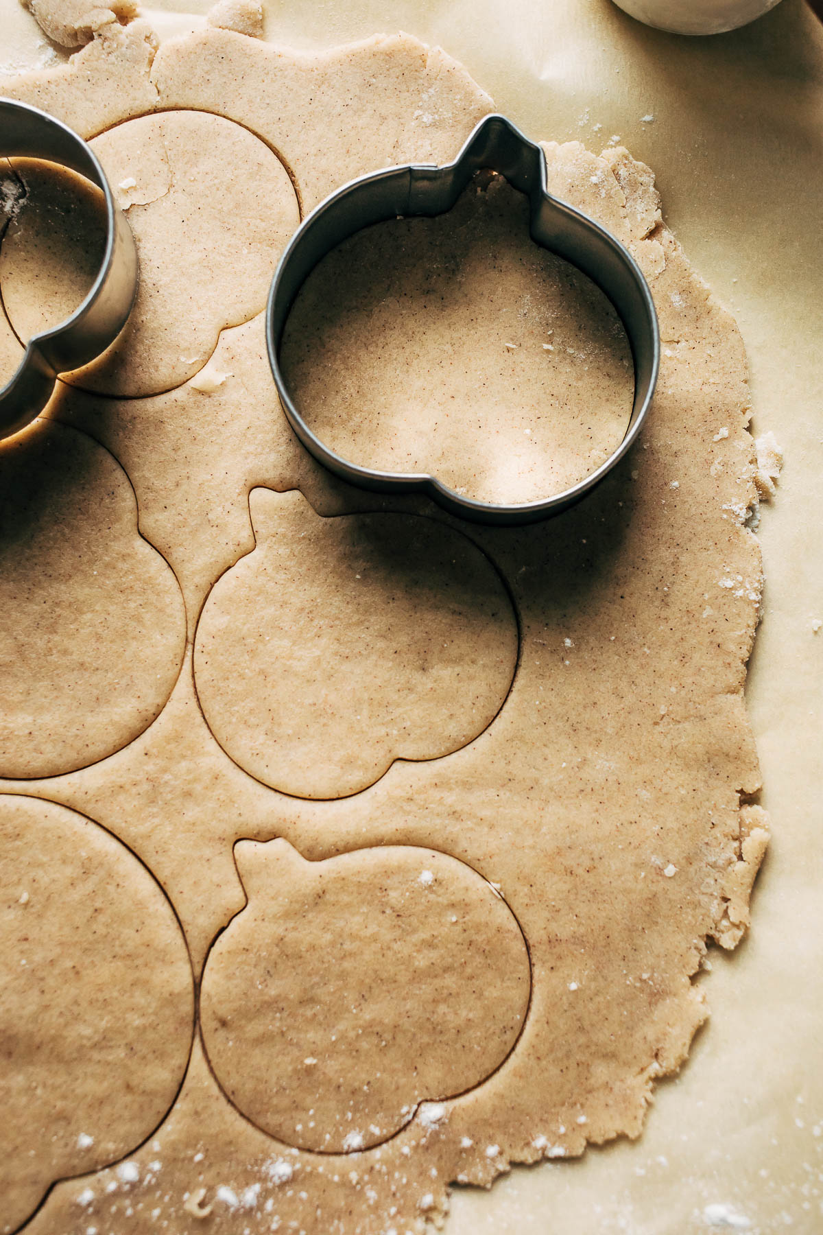 Pumpkin cookie cutters on rolled out dough.