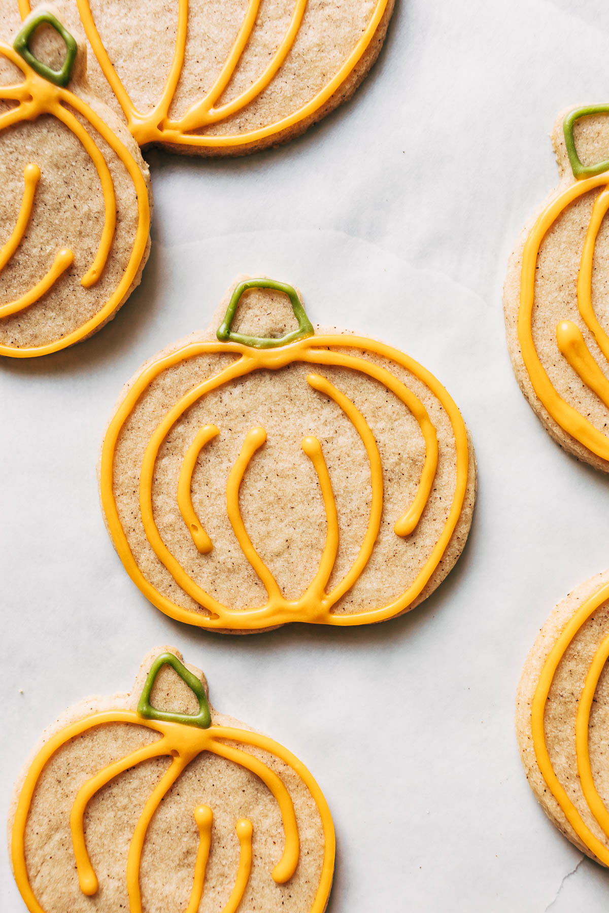Close up of decorated cookies on white parchment paper.