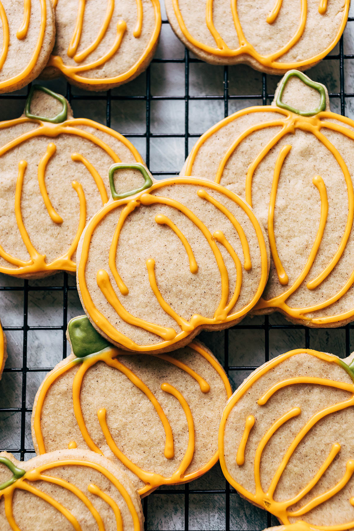 Close up of pumpkin shaped iced sugar cookies on a rack.