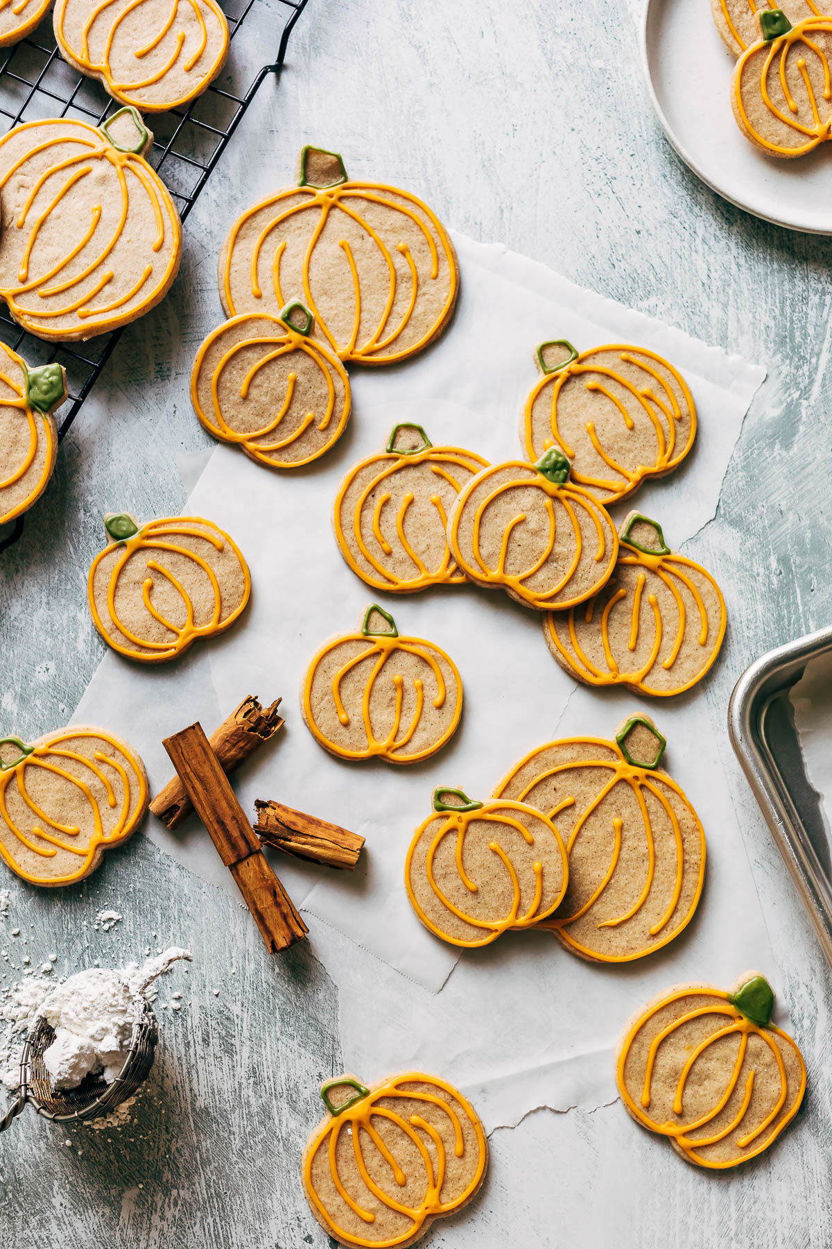 Pumpkin shaped sugar cookies with orange and green icing.