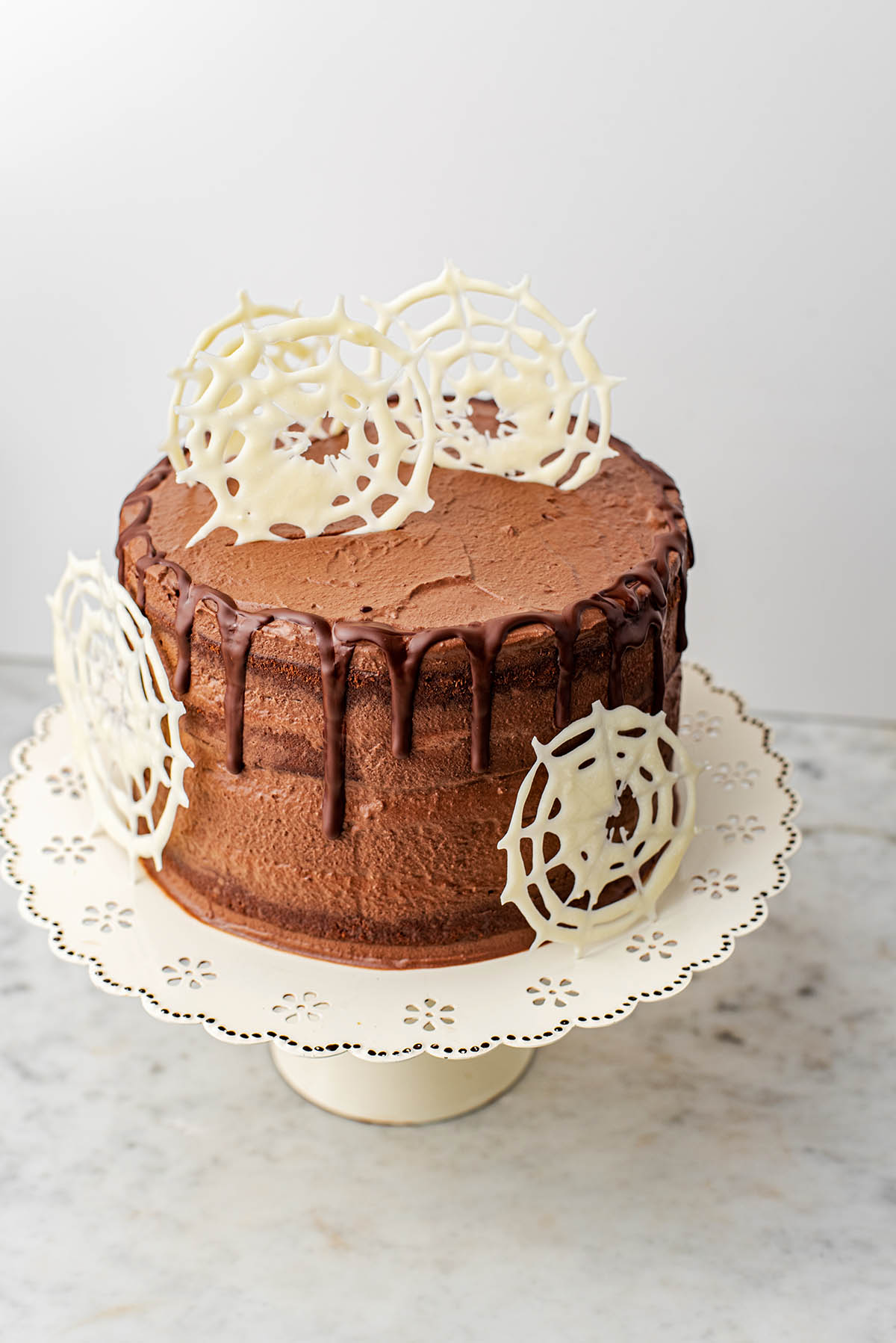 Chocolate cake with chocolate drip and white chocolate webs.