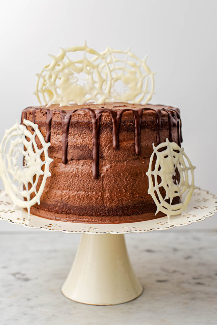 Four layer chocolate cake with white chocolate spiderwebs.