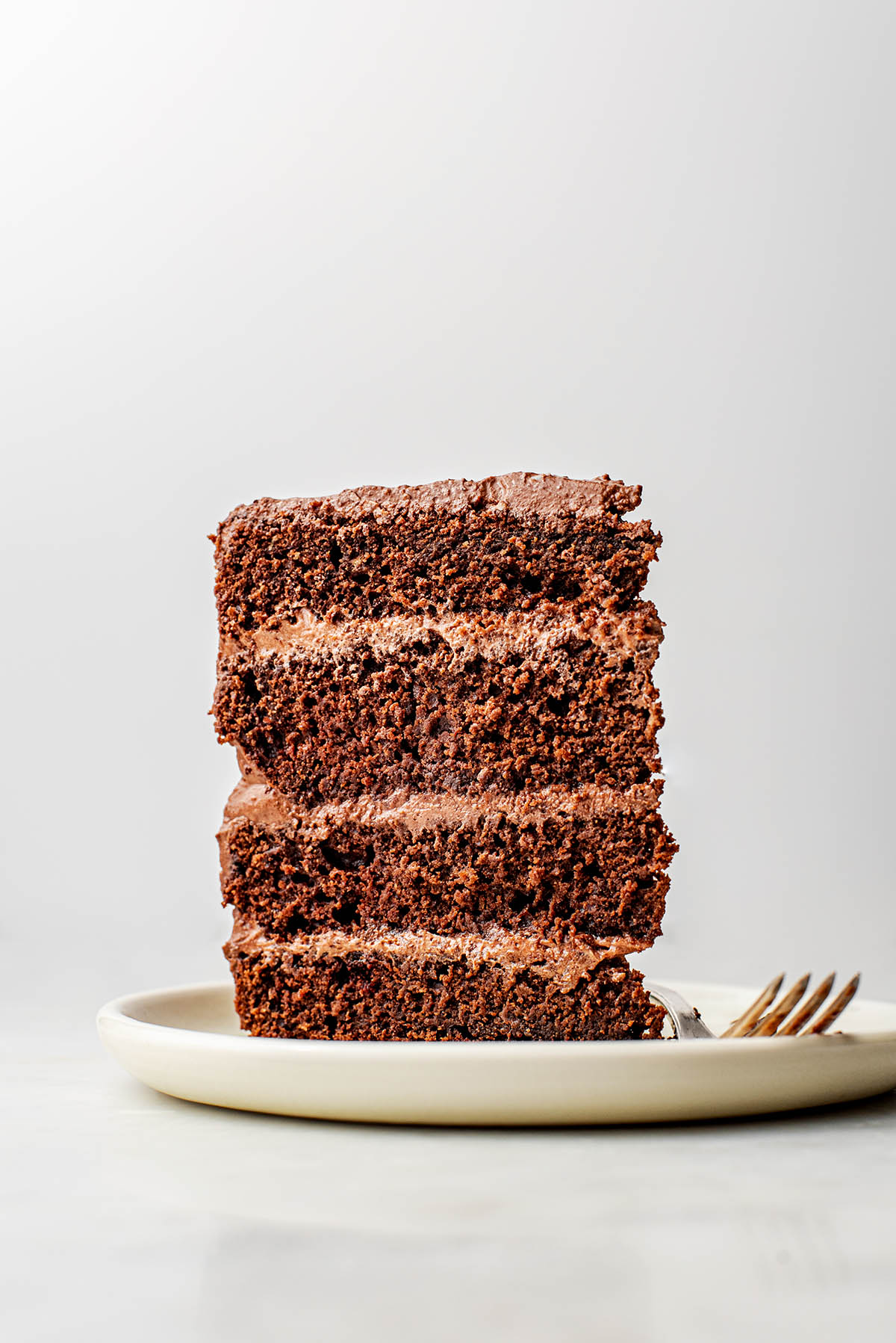 A slice of chocolate layer cake standing on a plate.