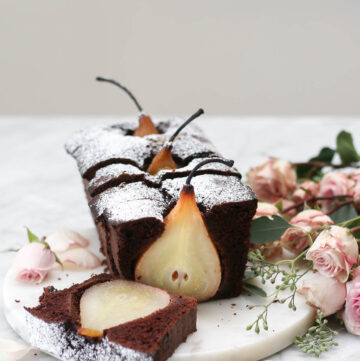 A sliced chocolate loaf cake on a marble platter with whole poached pears inside the loaf.