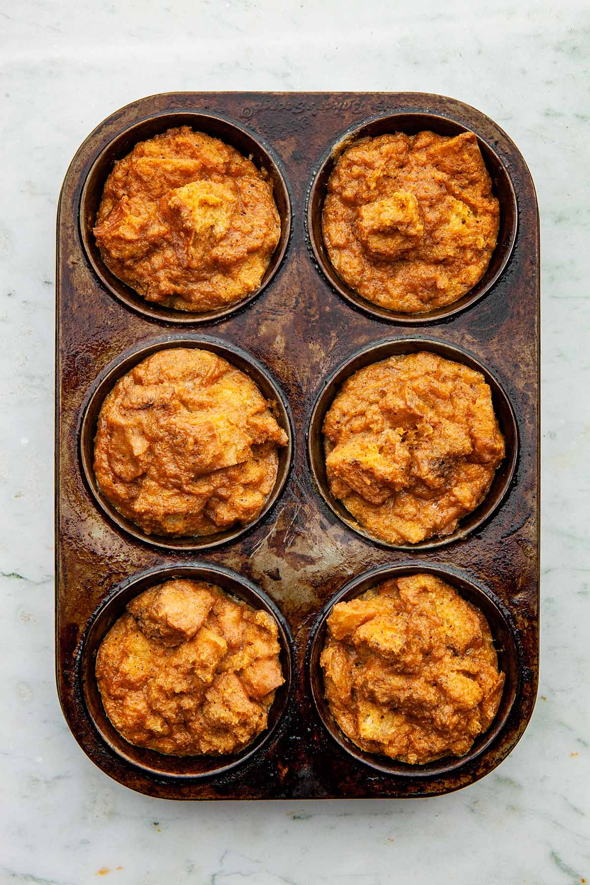 A six-cup jumbo muffin tin with baked pumpkin bread pudding inside each muffin cup.