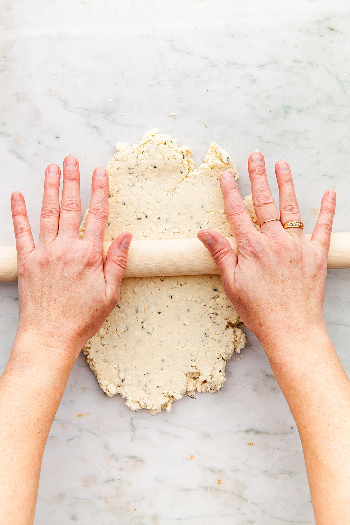 Hands rolling dough with a rolling pin.