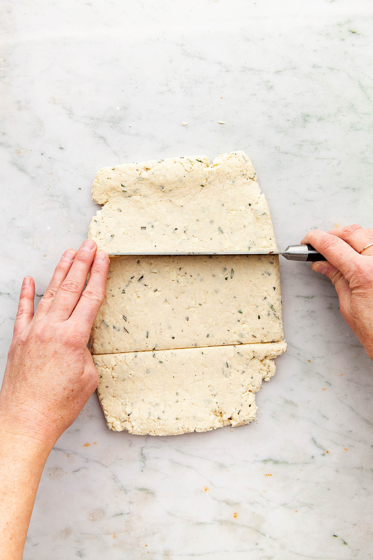 Hands using a long knife to slice dough into thirds.