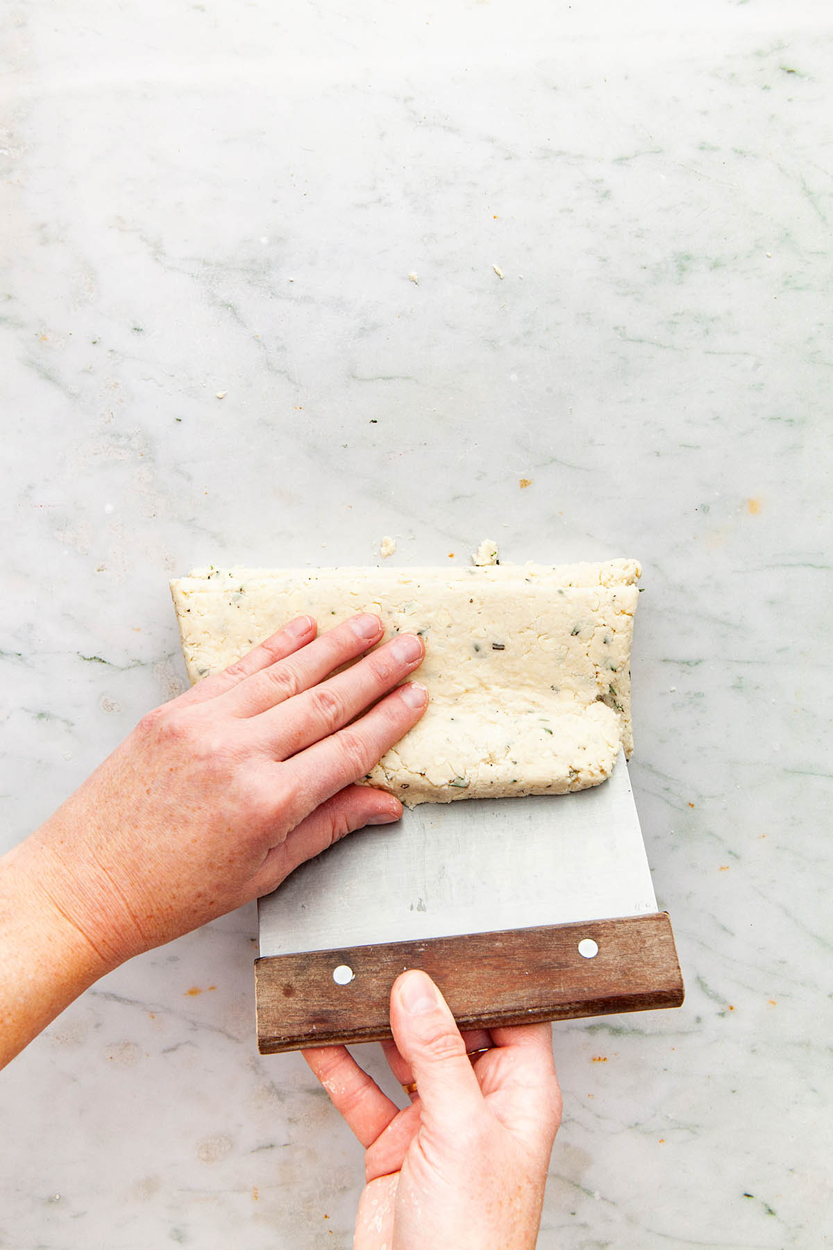 Hands stacking strips of dough on top of one another with a bench scraper.