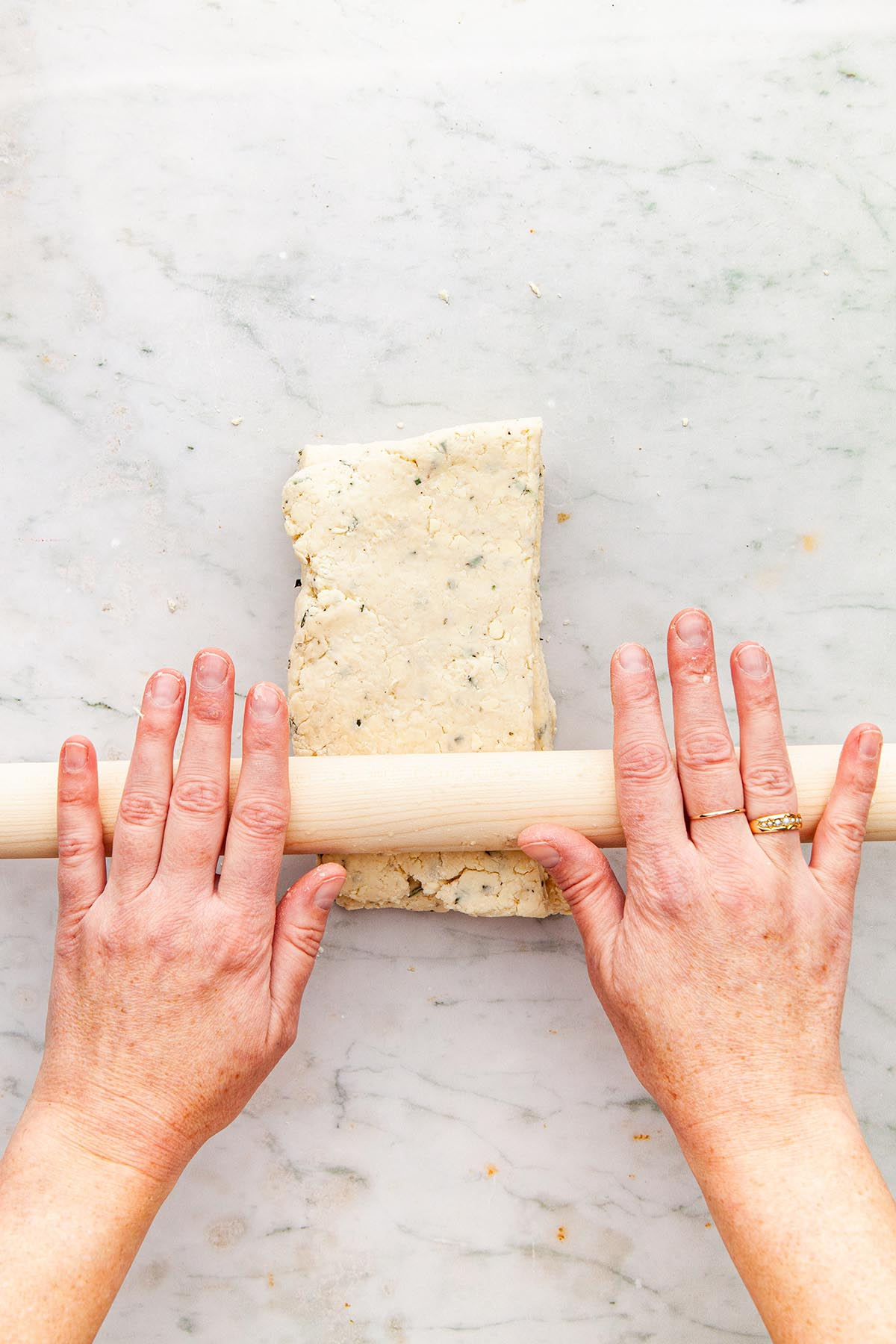 Hands rolling dough with a wooden pin.