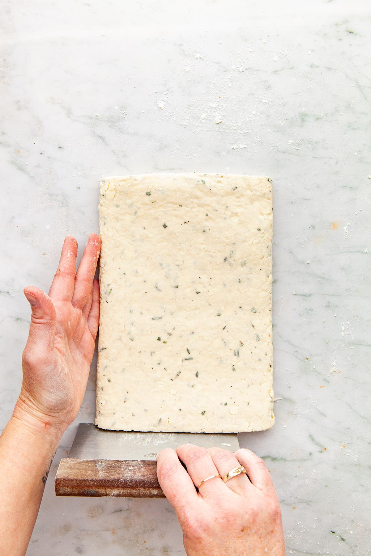 Hands smoothing the edge of rolled out dough with a bench scraper.