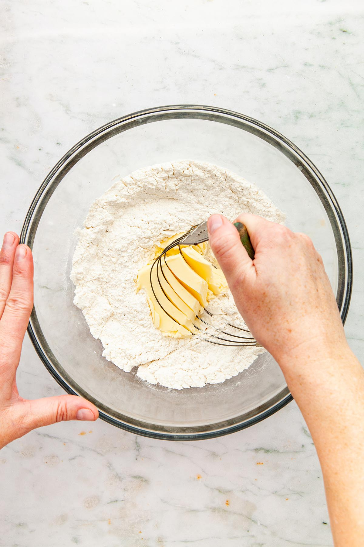 Hands using a pastry blender to cut butter into flour.