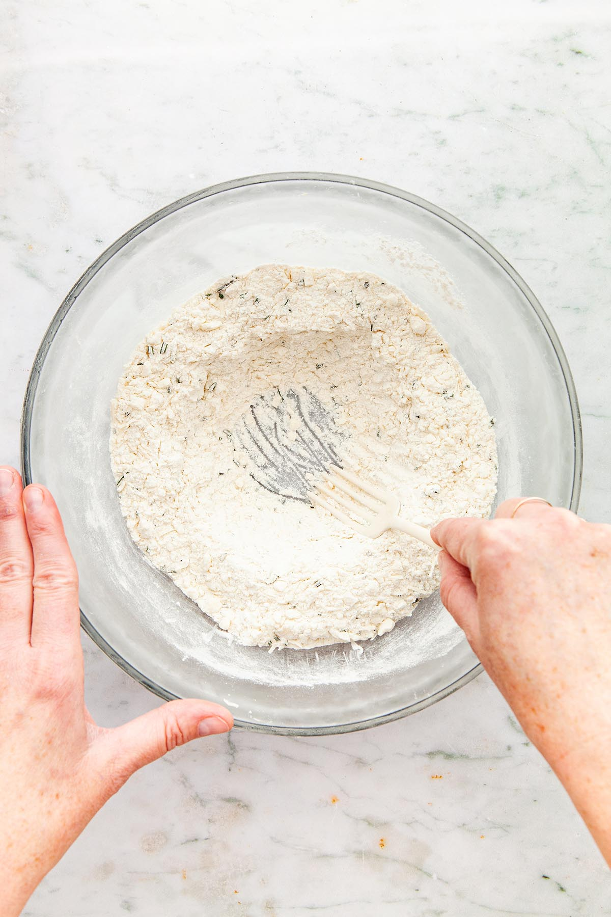 Hands making a well in the middle of a bowl of flour with a fork.