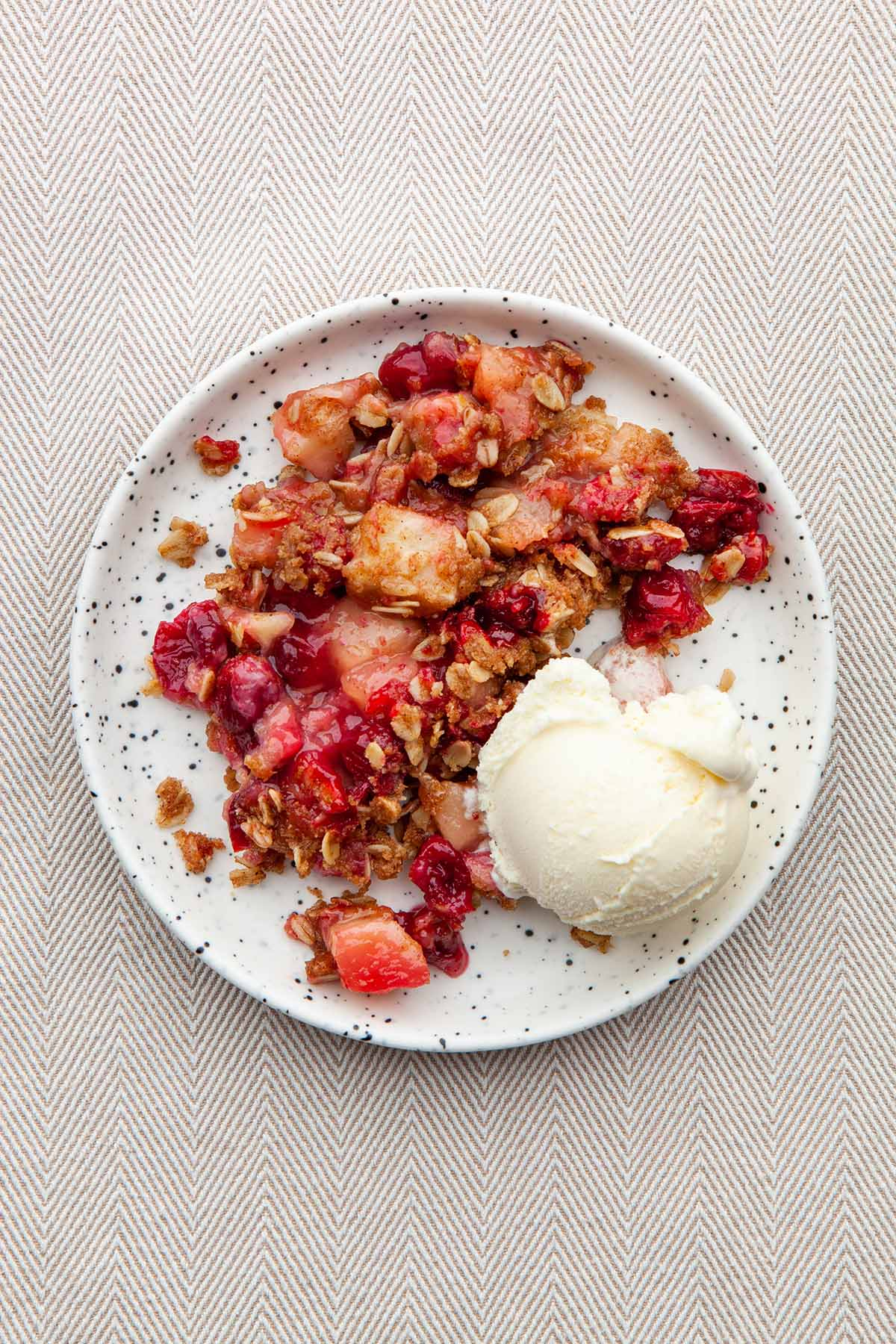 A plate of cranberry apple crisp topped with ice cream.