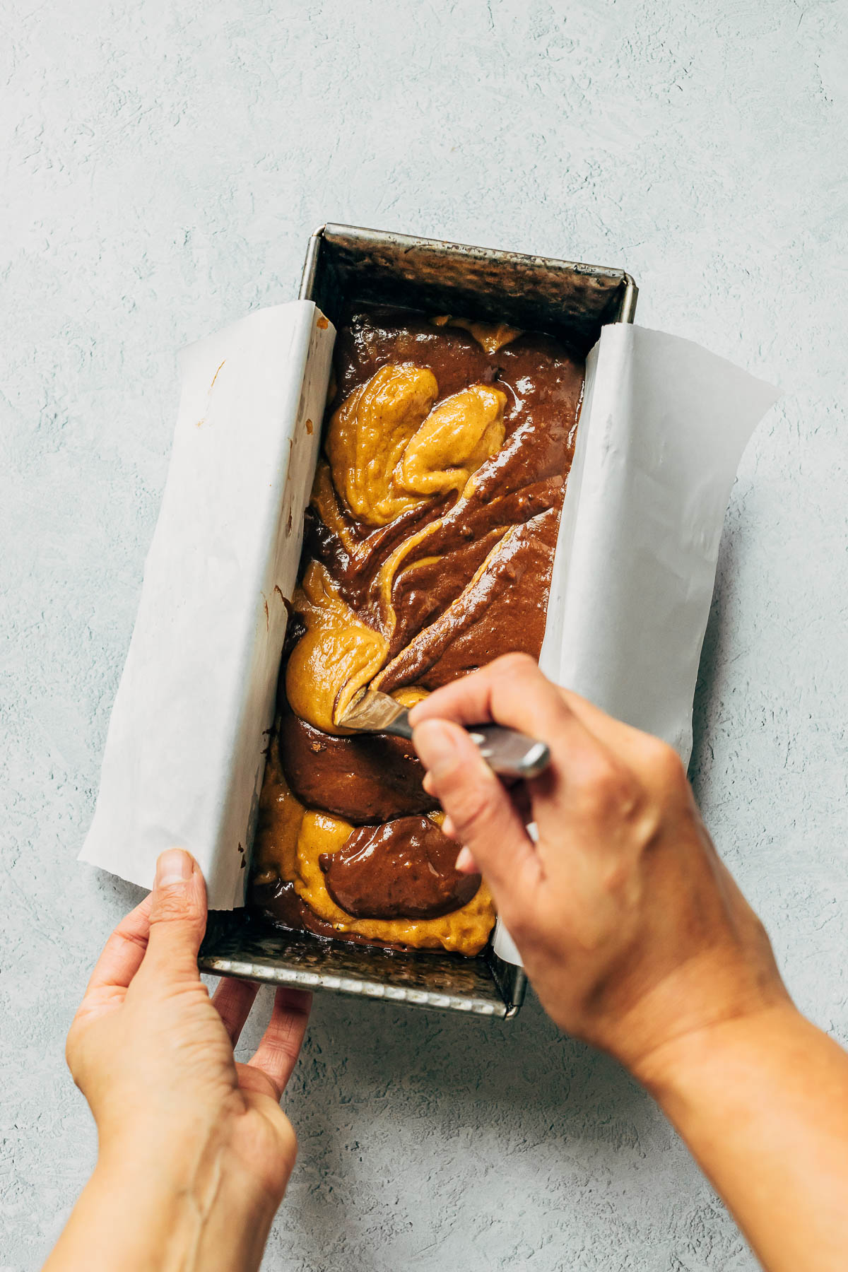 A hand swirling loaf batter in a baking tin with a butter knife.