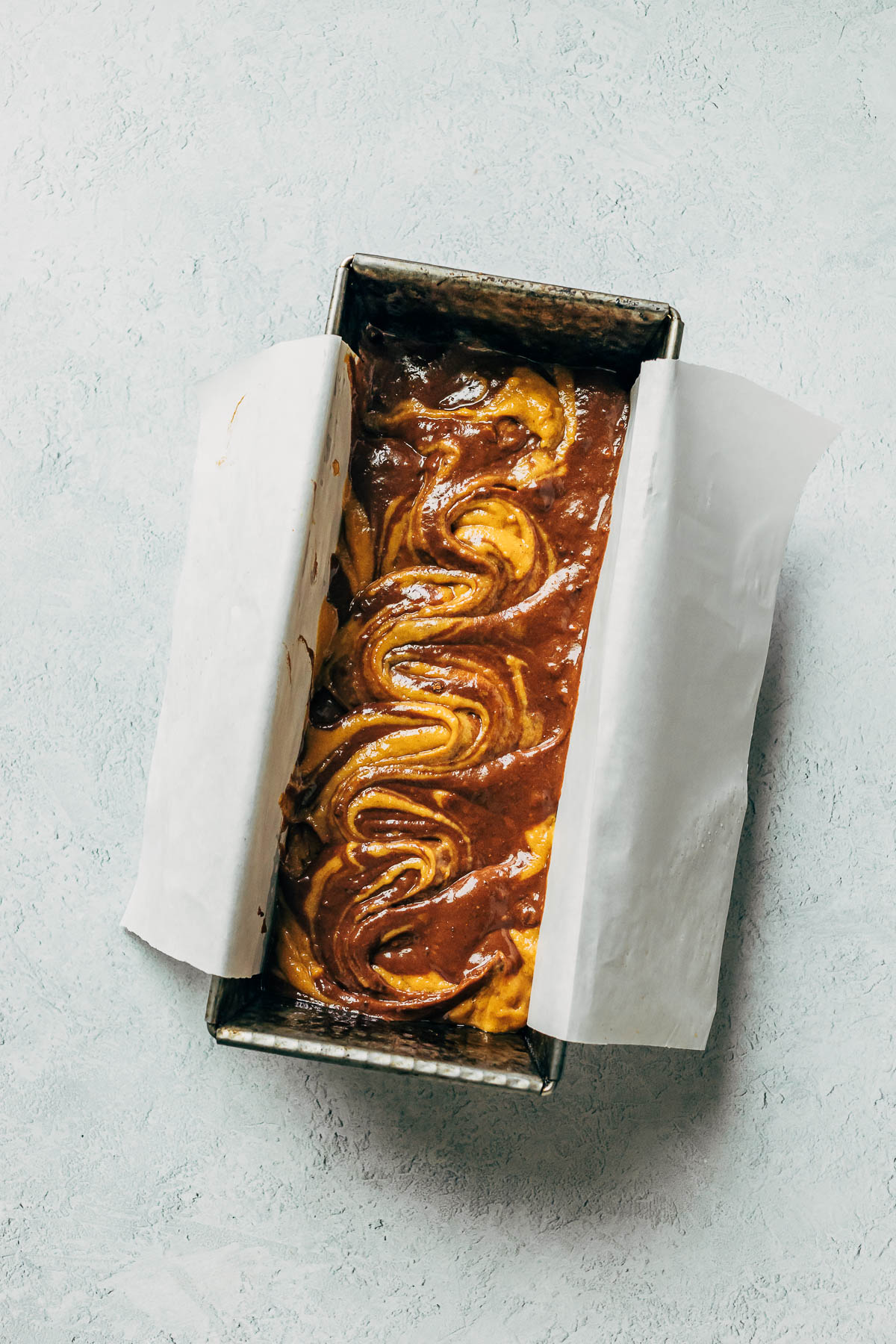 Overhead image of swirled loaf batter in a baking tin lined with parchment paper.