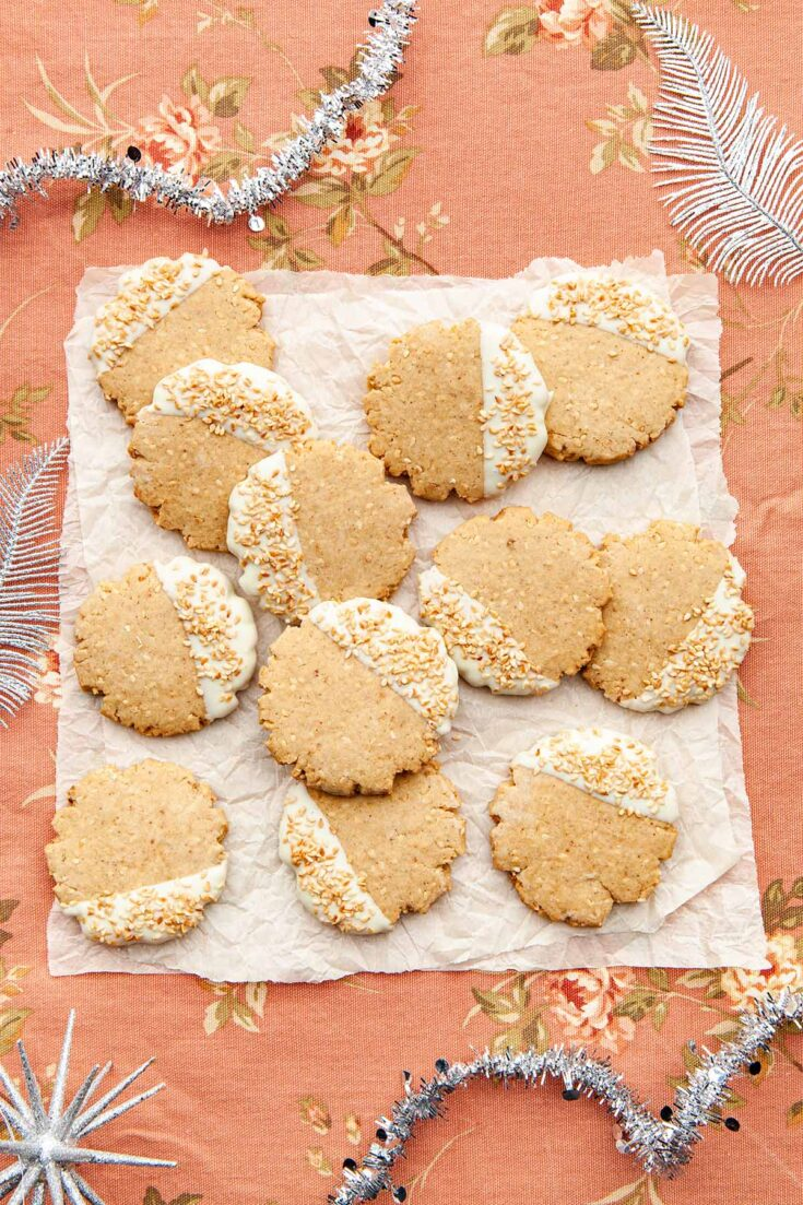 A batch of brown butter sesame seed cookies on two layers of crinkled parchment paper on a pink fabric background with silver holiday decorations around the perimeter.