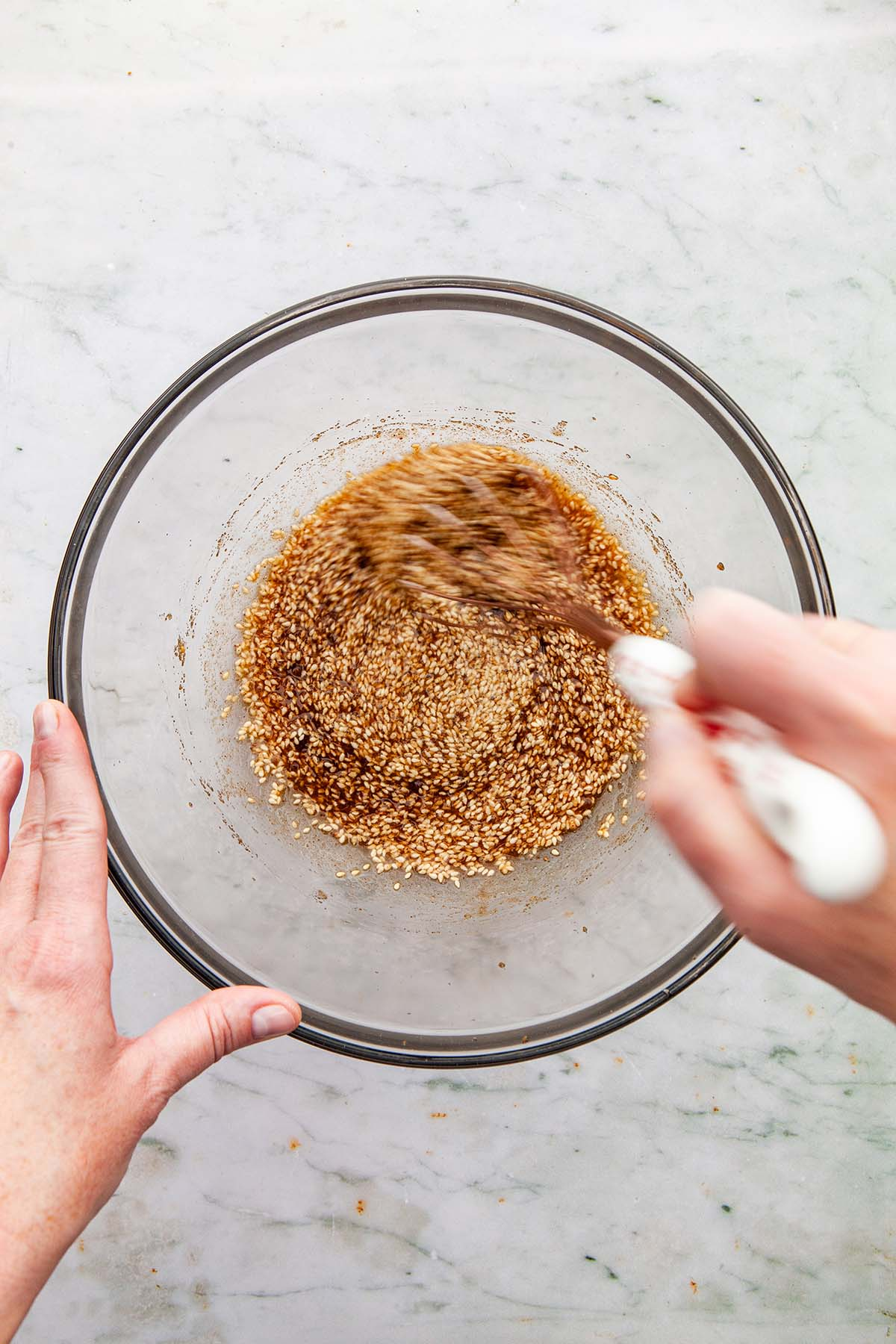 A hand whisking brown sugar with brown butter and sesame seeds.