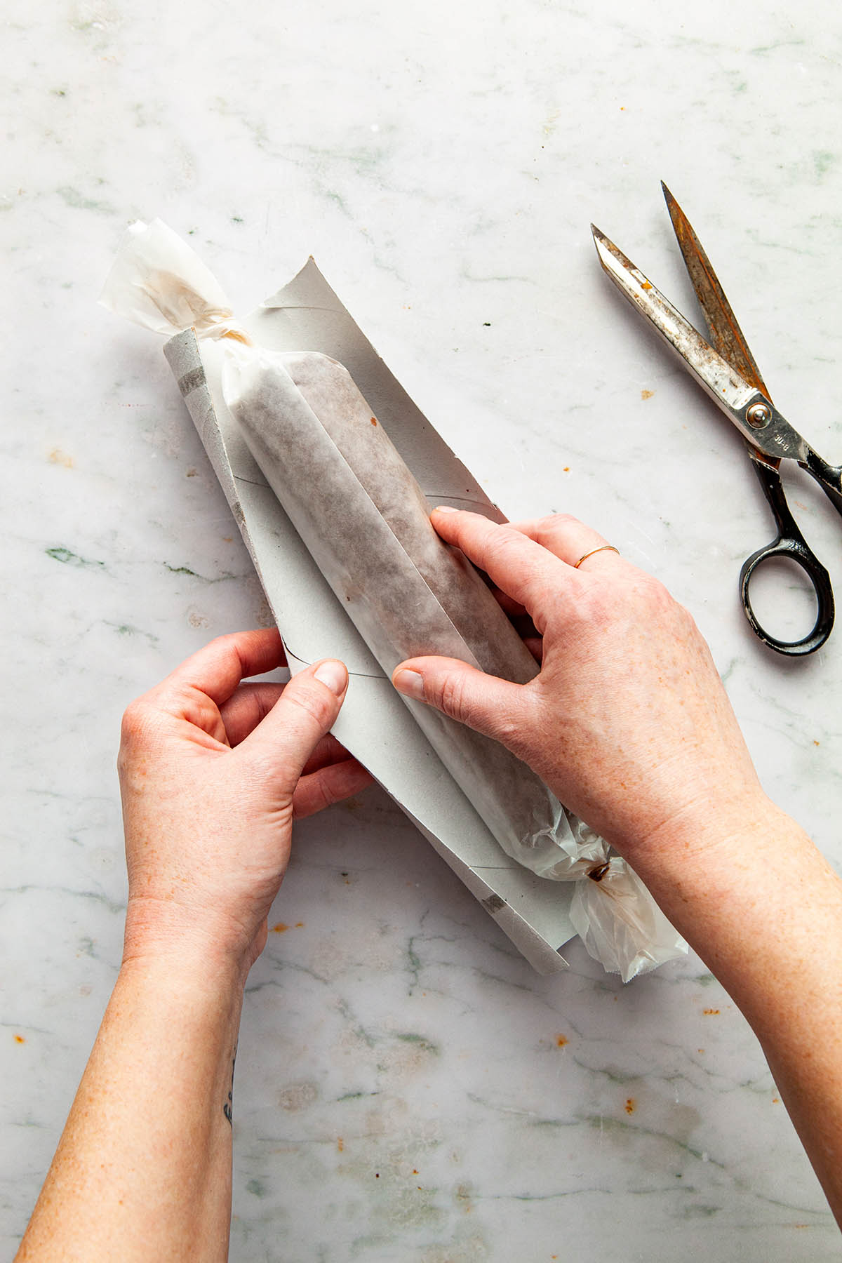 Hands placing a wrapped log of cookie dough in a paper towel tube cut open with scissors.