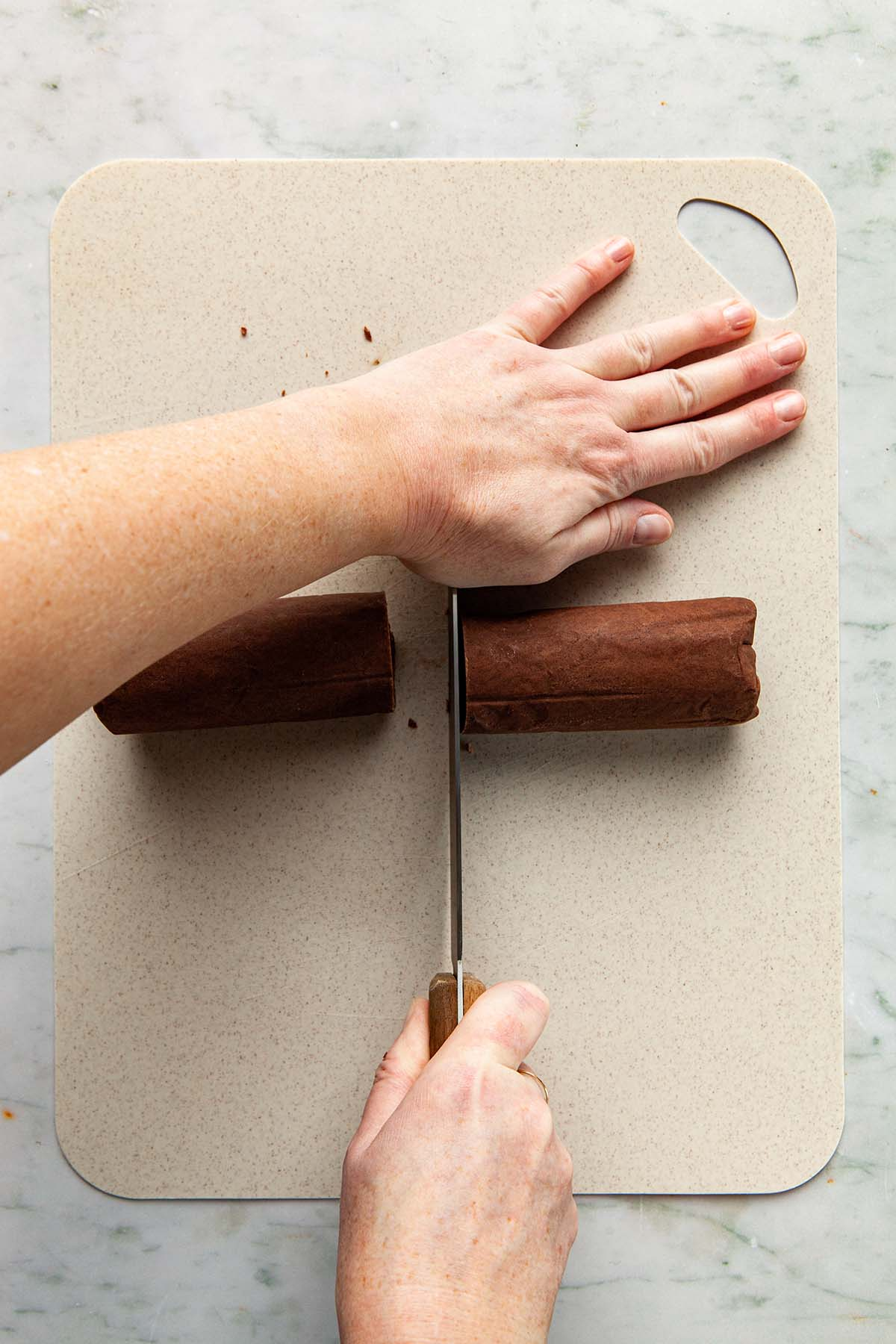 Hands slicing a cookie dough log with a knife.