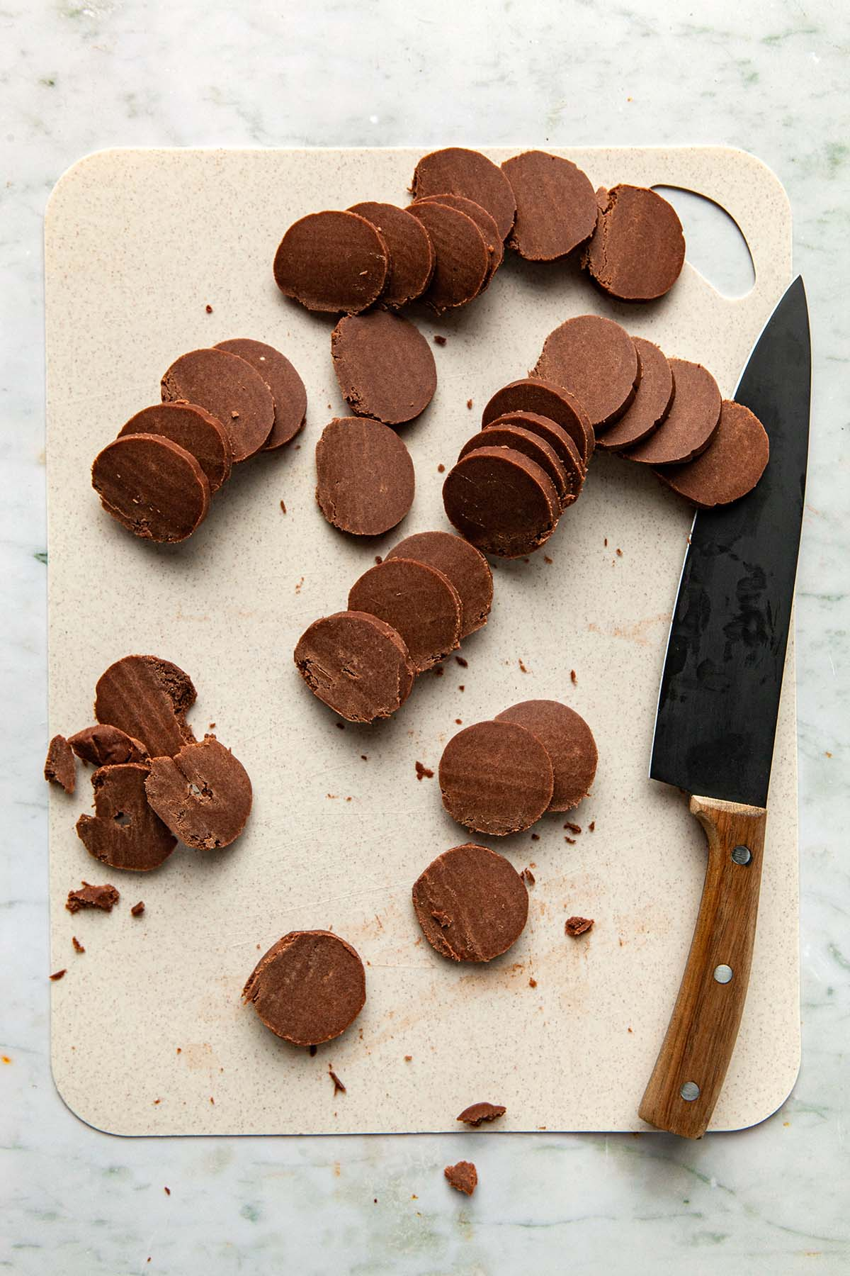 Sliced cookies on a beige cutting board next to a alrge wood handled chef's knife.