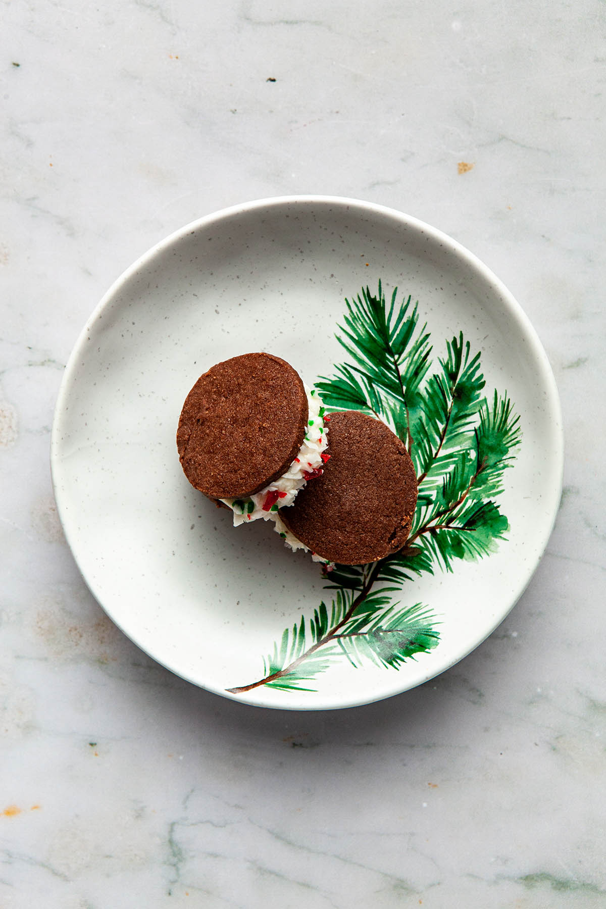 Two chocolate shortbread sandwich cookies on a small white plate with an evergreen branch painted on it.