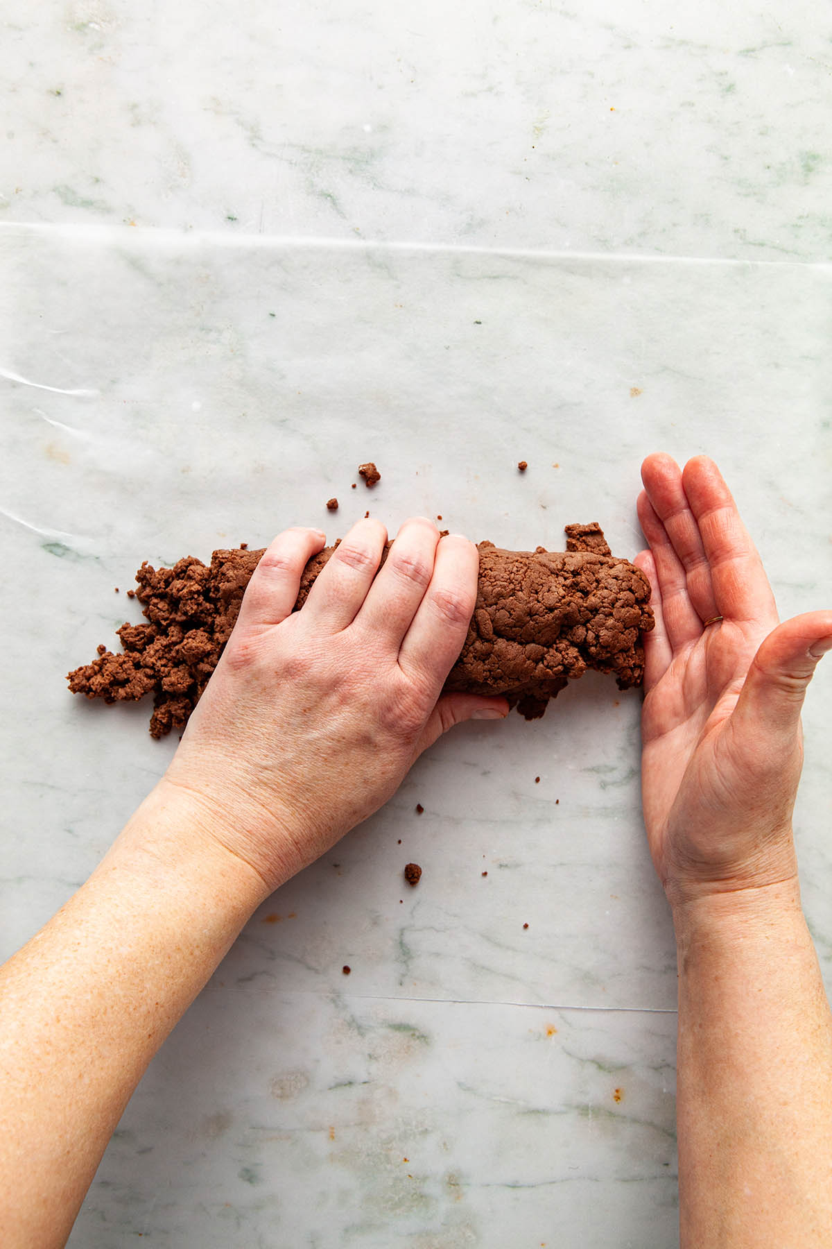 Hands shaping chocolate cookie dough into a log.