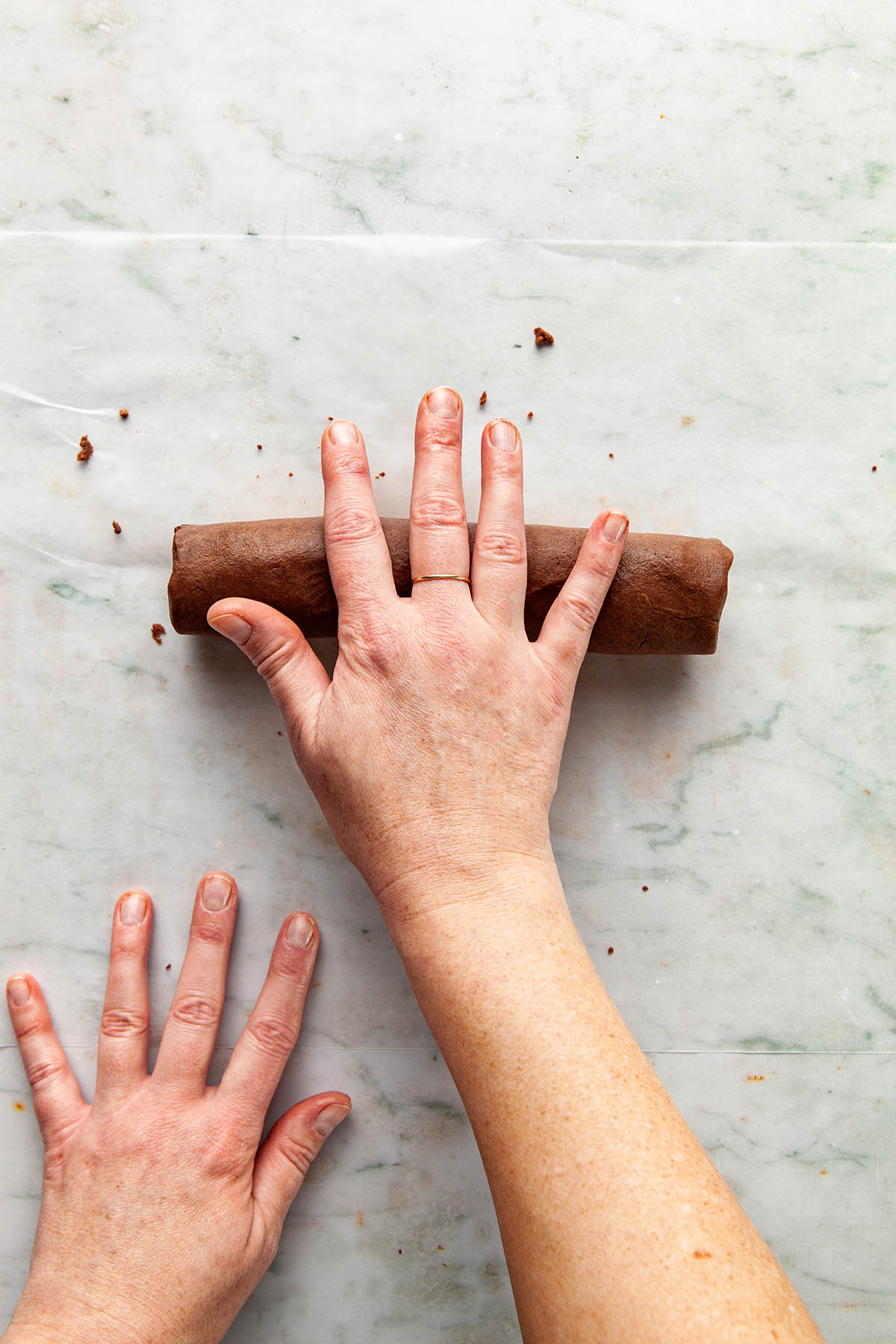 Hands rolling a log of chocolate cookie dough to make it smooth.